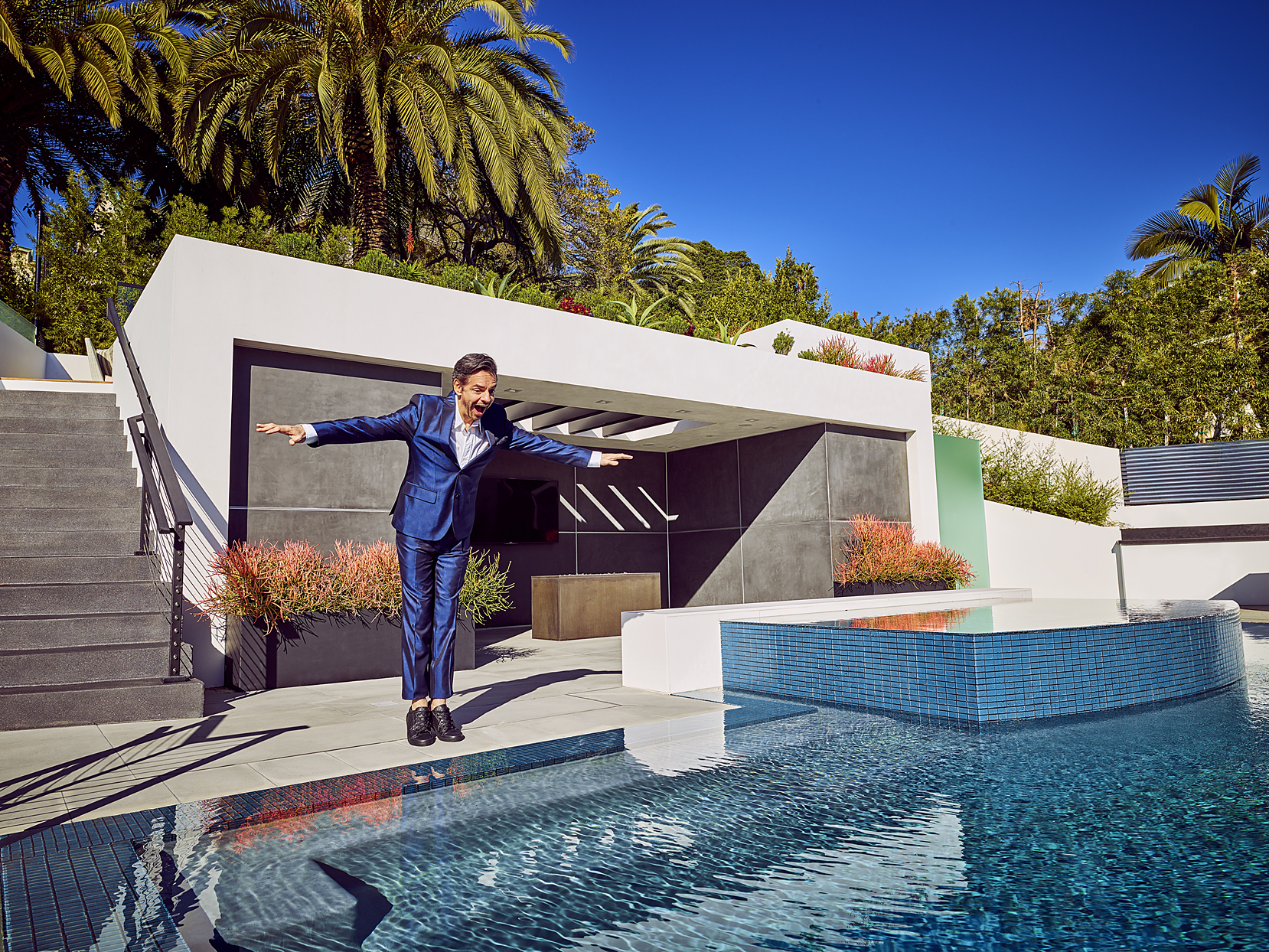 Mark DeLong - Celebrity Photographer - Actor in a blue suit about to fall into a pool.