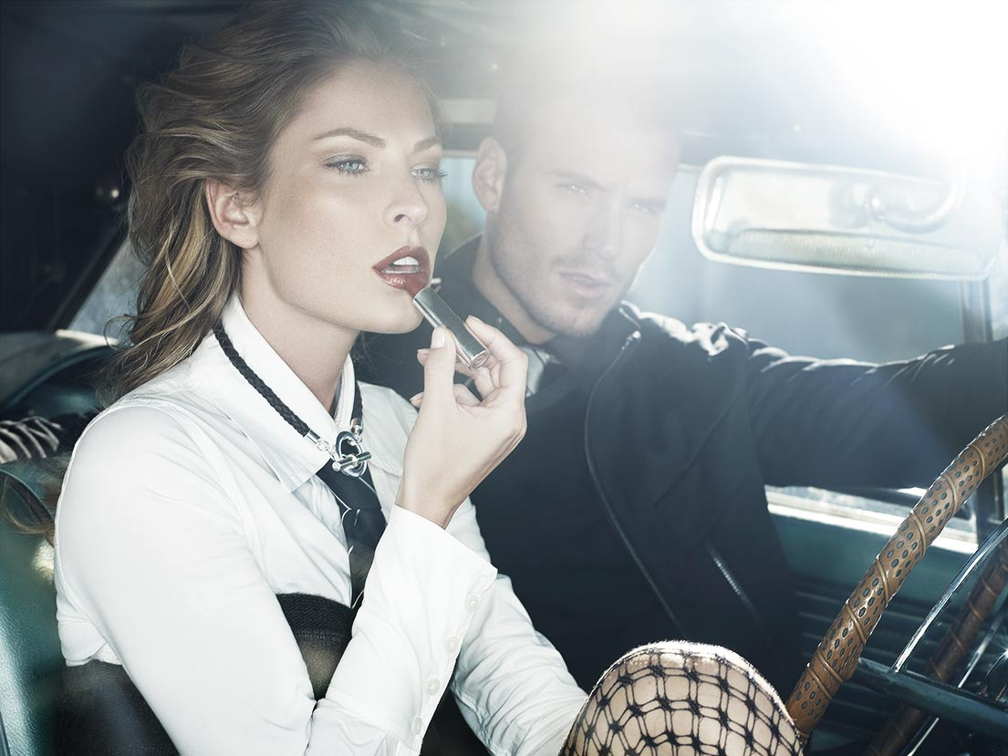 Mark DeLong - Lifestyle Photography - A man and woman sitting in a retro car while the woman applies lipstick