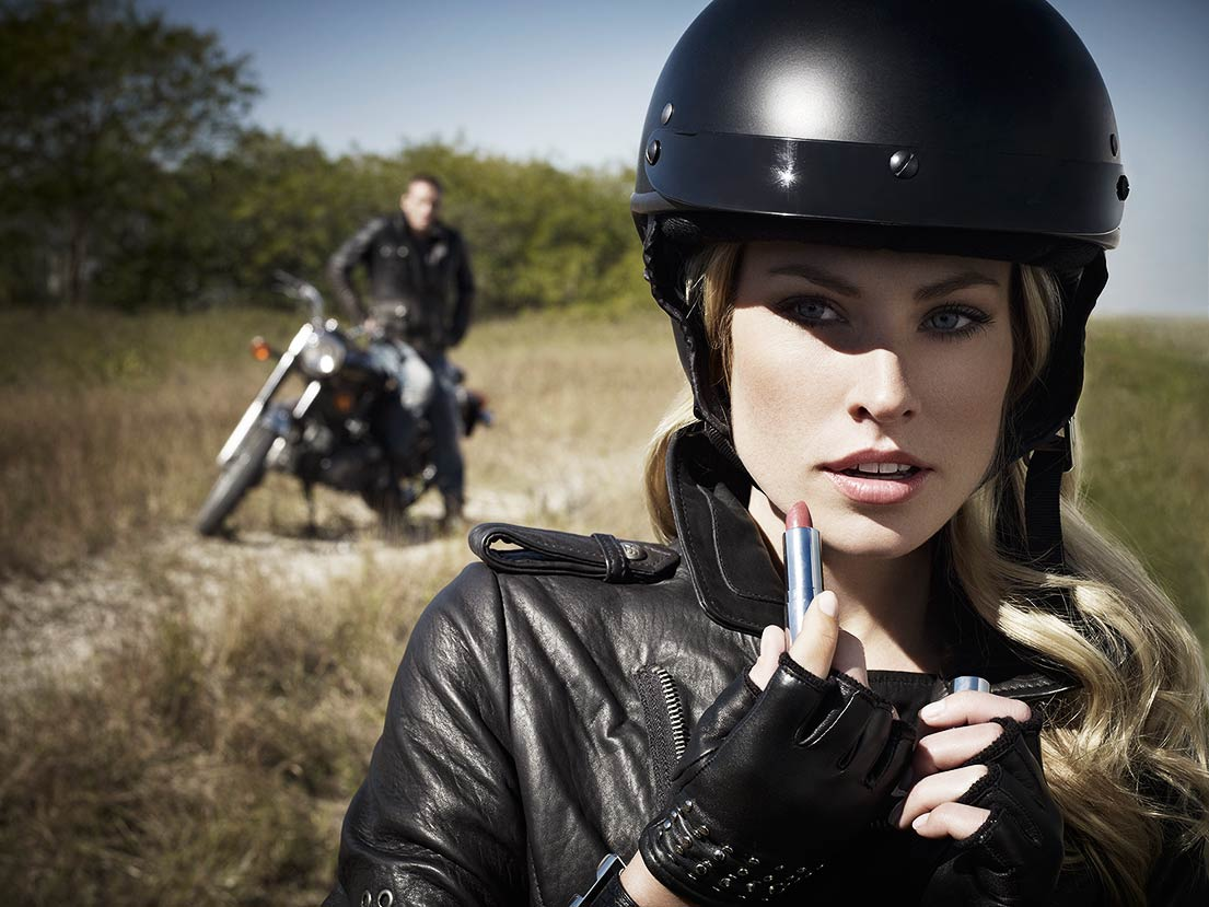 Mark DeLong - Lifestyle Photography - A woman in a motorcycle helmet applying lipstick and a man in the background on a motorcycle