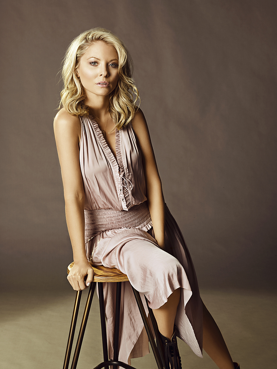 Mark DeLong - Celebrity Photographer - Actress in a pink dress sitting on a wood and metal stool.