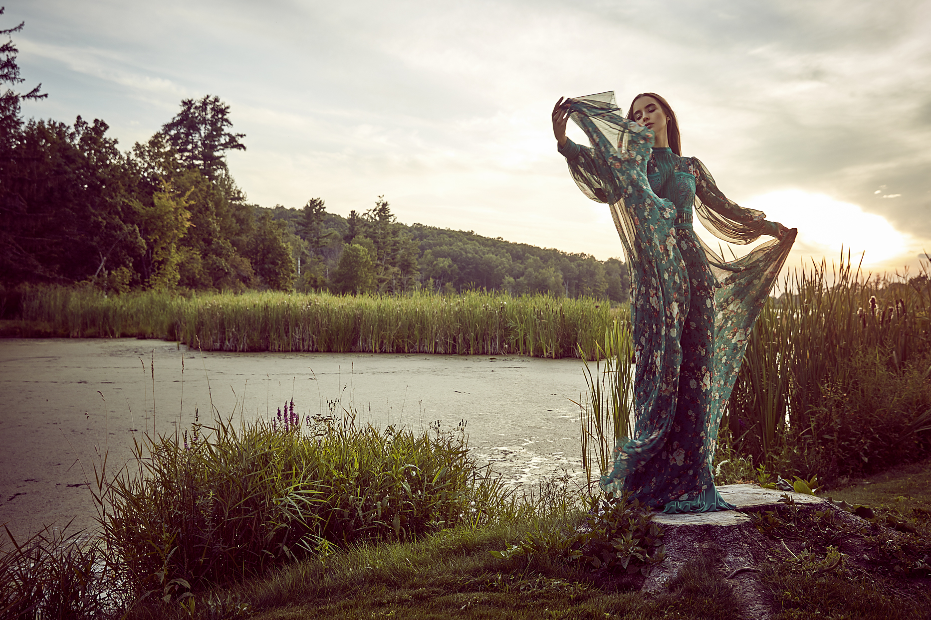 Woman waving elegant teal blue dress in front of marsh with high grass in background - Mark DeLong: Fashion Gallery
