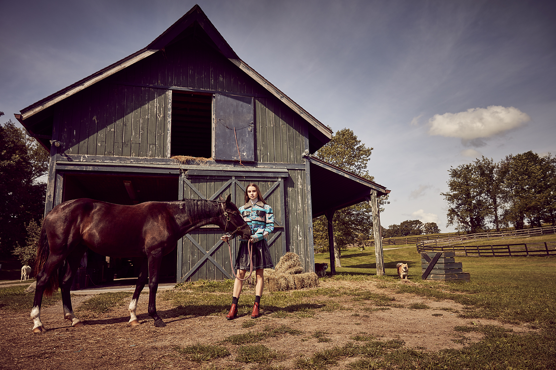 Woman with light blue jacket tending to a dark brown horse in front of an old barn - Mark DeLong: Fashion Gallery