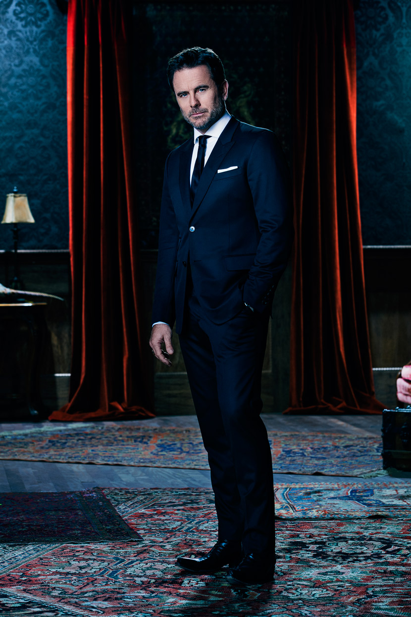 Mark DeLong - Celebrity Photographer - Actor in a blue suit standing between two red curtains.