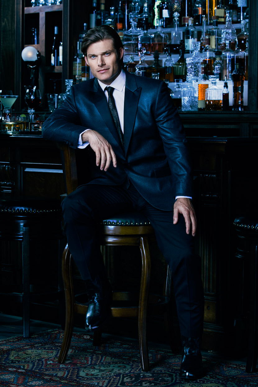 Mark DeLong - Celebrity Photographer - Actor in a blue suit sitting at a bar.