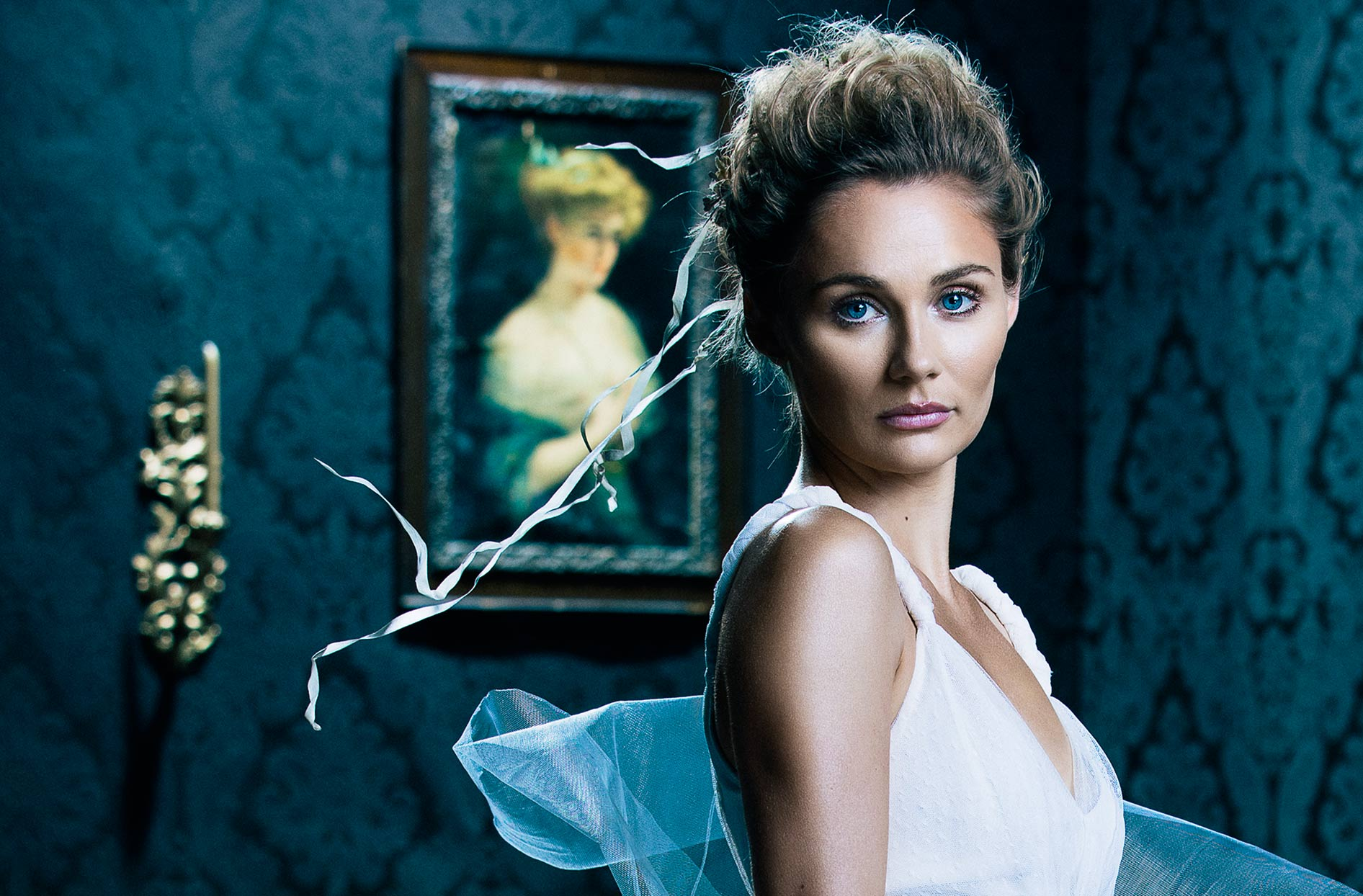Mark DeLong - Celebrity Photographer - Actress in a white dress posing in living room with painting in background.