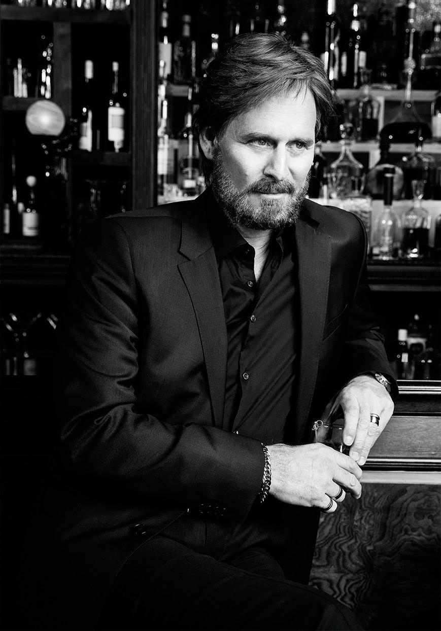 Mark DeLong - Celebrity Photographer - Black and white photo of a middle age actor in a black suit at a bar.