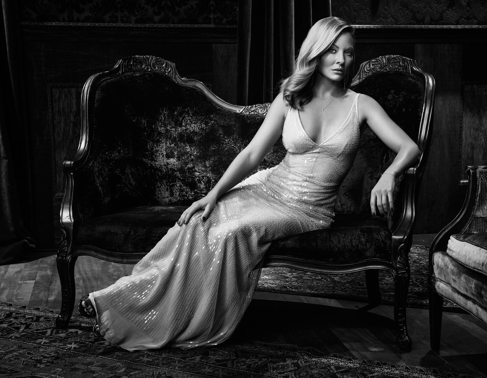 Mark DeLong - Celebrity Photographer - Black and white photo of an actress in a white dress sitting on a piece of antique furniture.