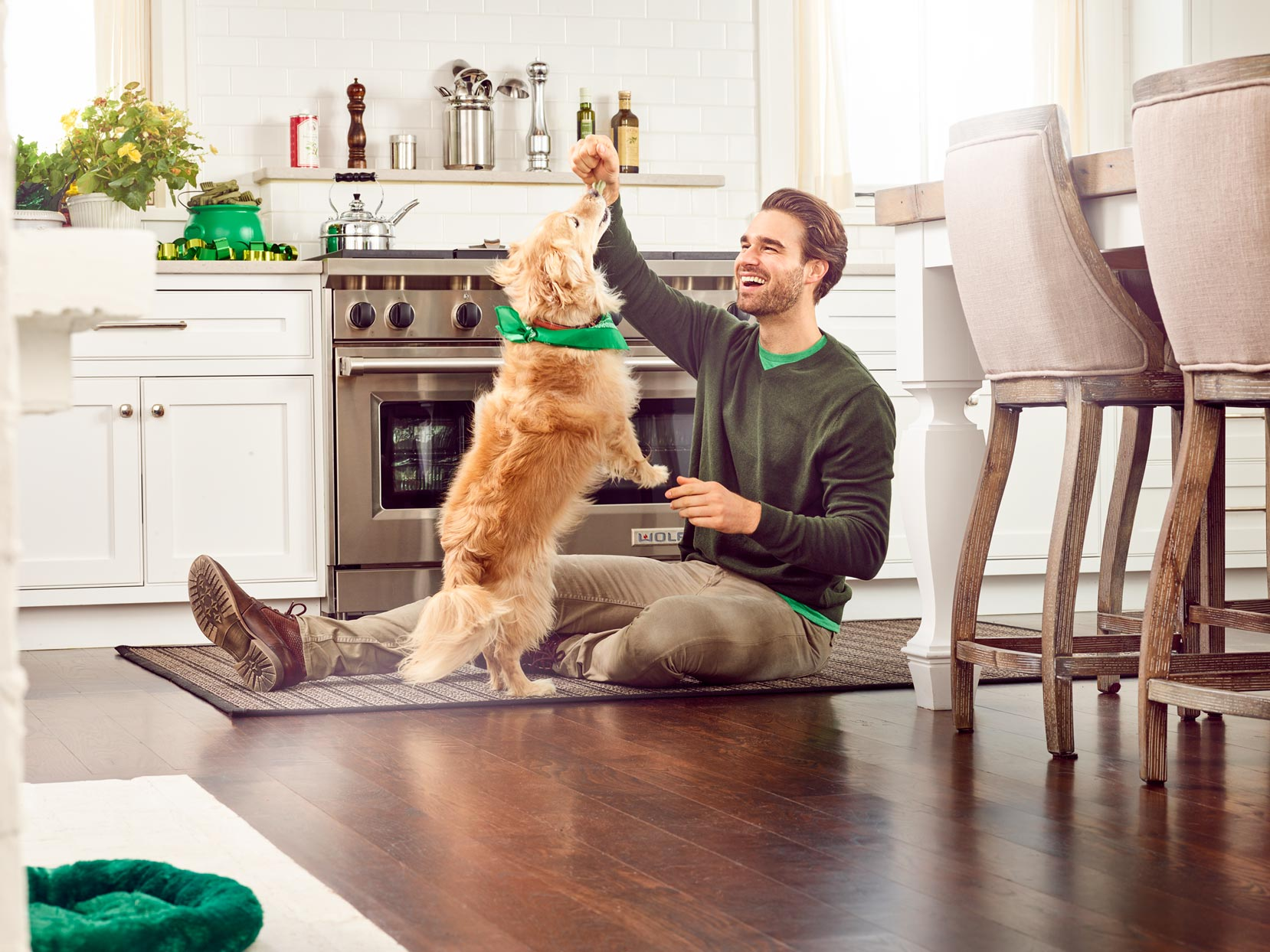 Mark DeLong - Commercial Photography - Man playing on kitchen floor with his golden retriever.