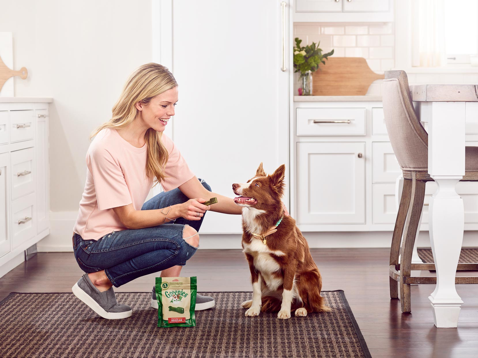 Mark DeLong - Commercial Photography - Woman giving her dog a treat in the kitchen.