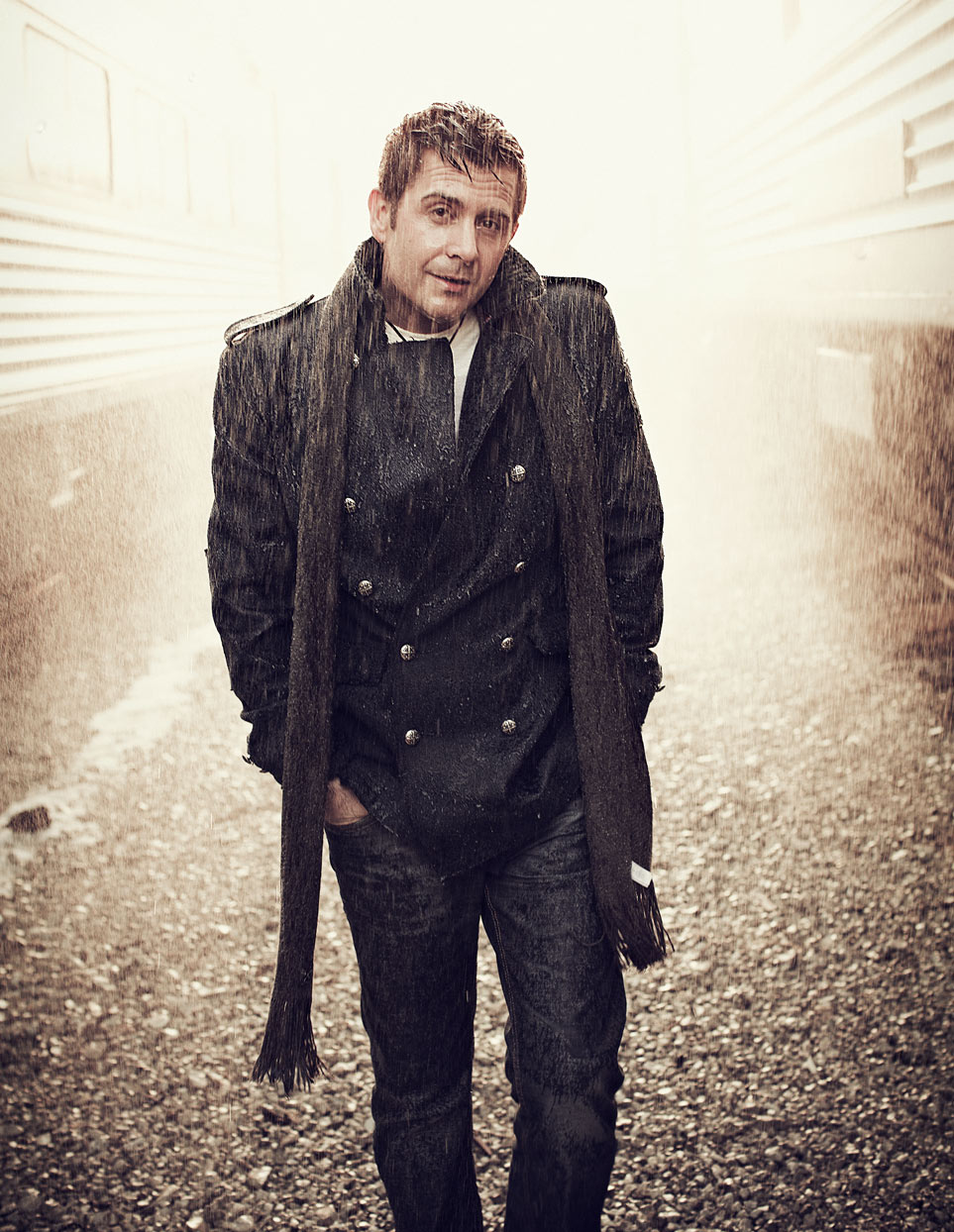 Mark DeLong - Celebrity Photographer - Actor walking between rail cars in dreary weather.