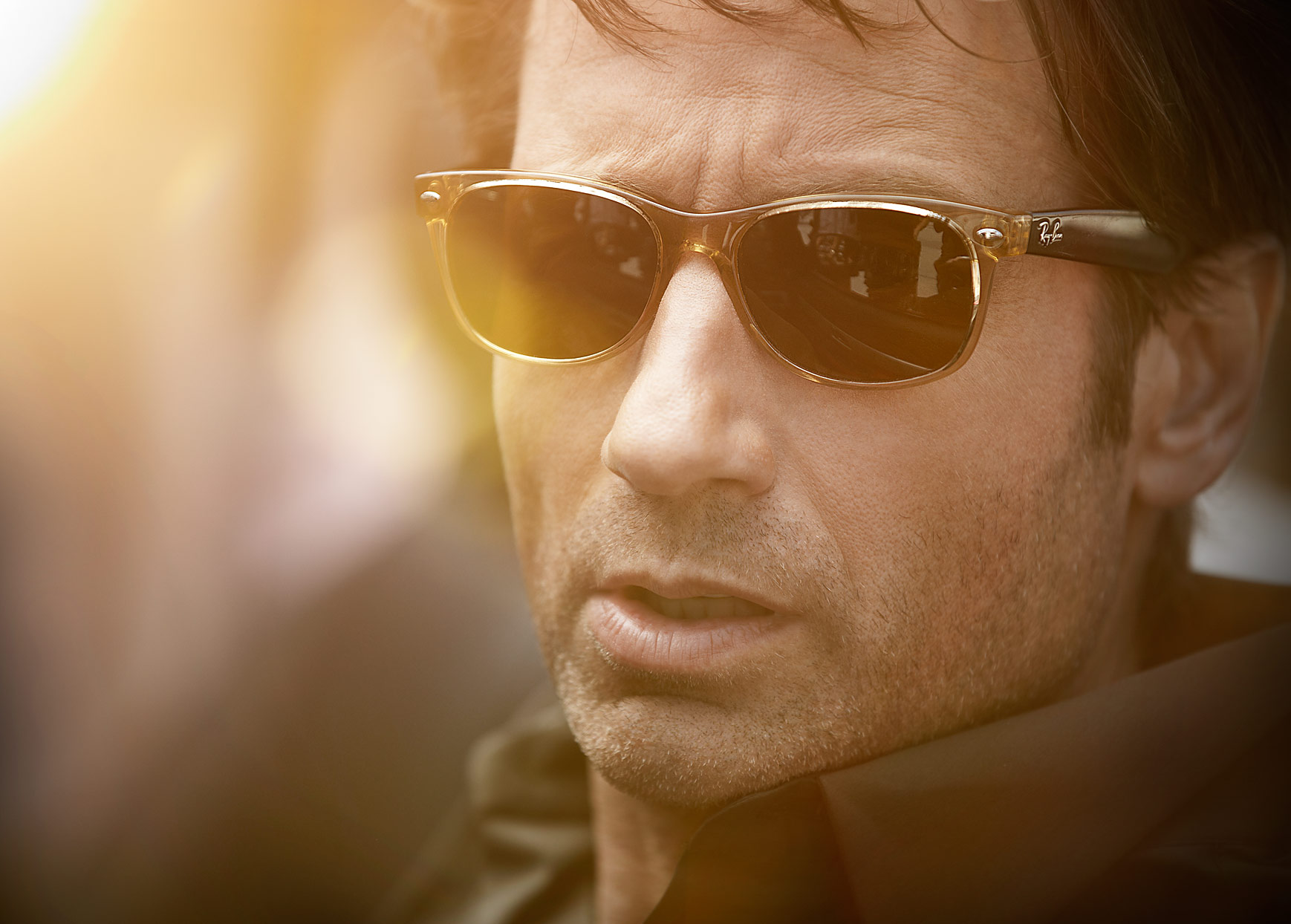 Mark DeLong - Celebrity Photographer - Actor wearing dark shades looks away from light.