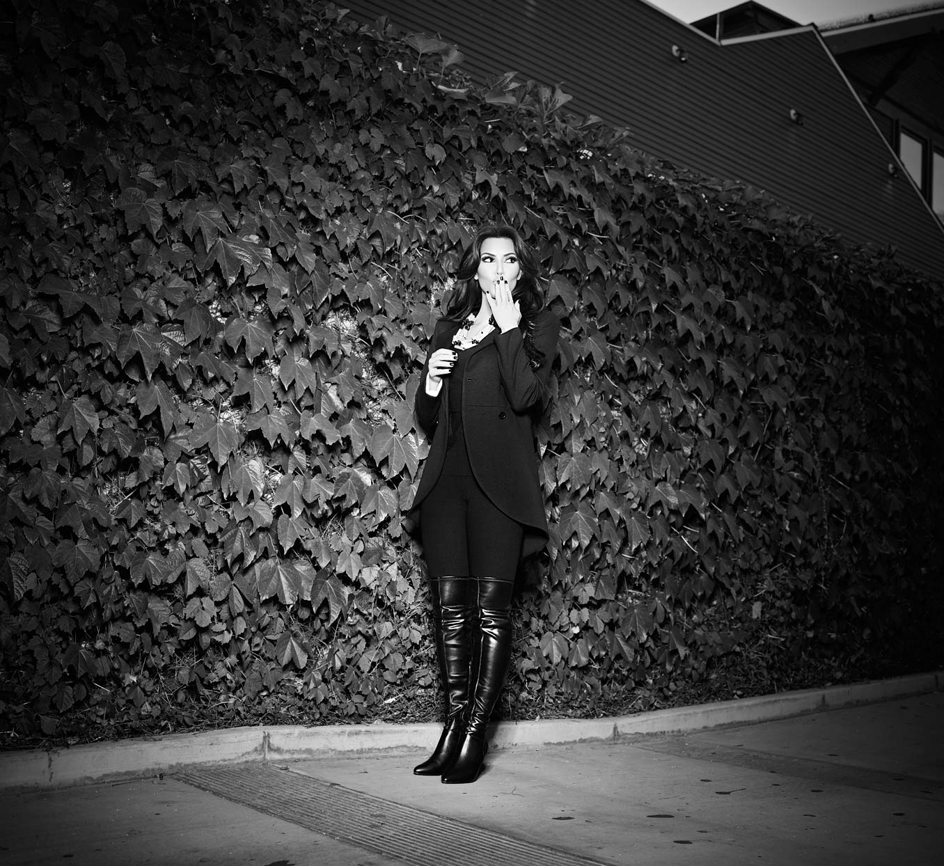 Mark DeLong - Celebrity Photographer - Black and white photo of a female celebrity standing in front of bushes in the spotlight.