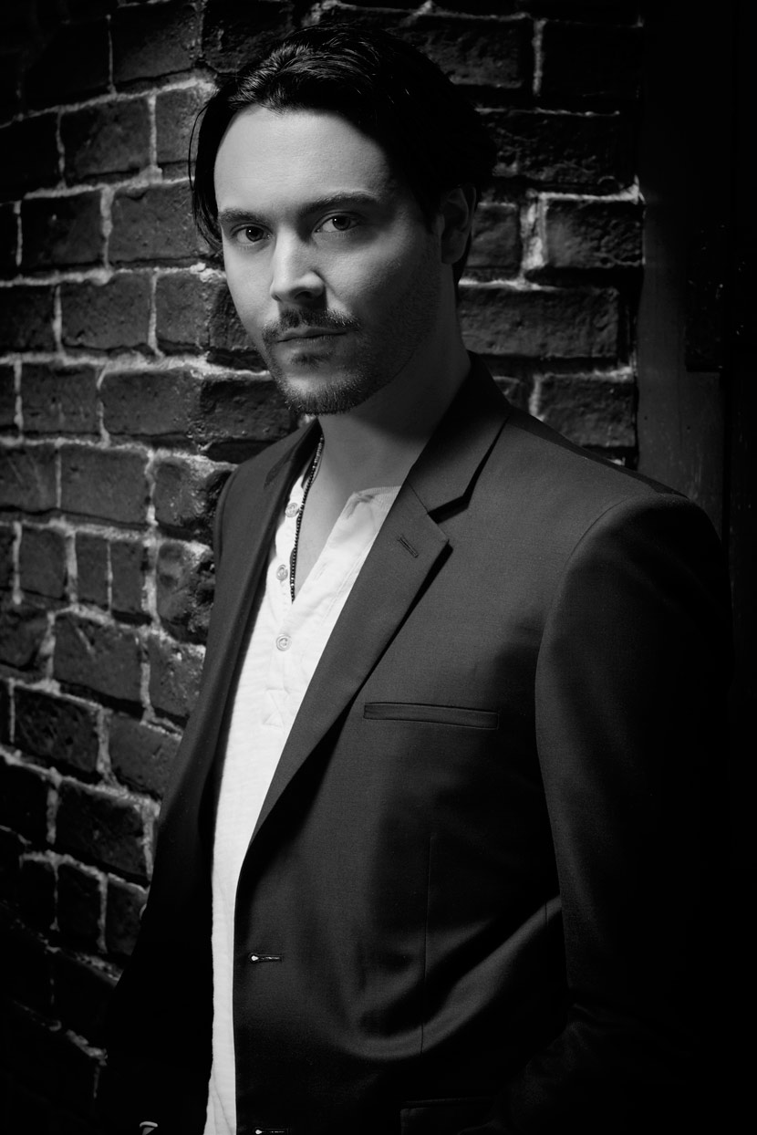 Mark DeLong - Celebrity Photographer - Black and white photo of actor in a blazer leaning against a brick wall.