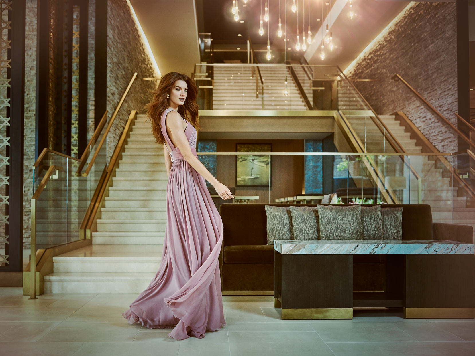 Mark DeLong - Commercial Photography - Woman walking by staircase in pink gown.