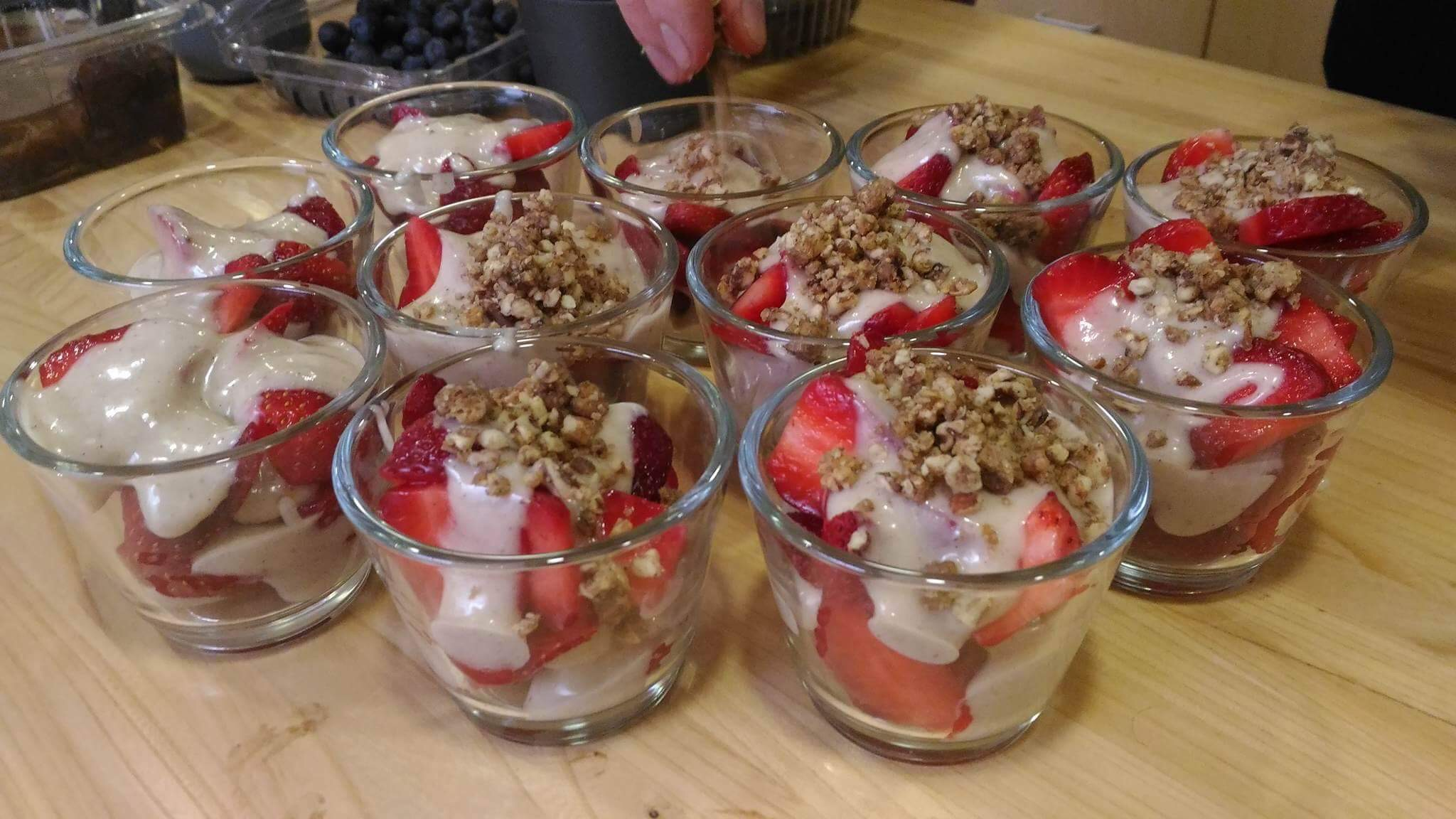 Layered Strawberries, sweet vanilla cream and mulberry-pecan crumble. Adding the finishing touches.