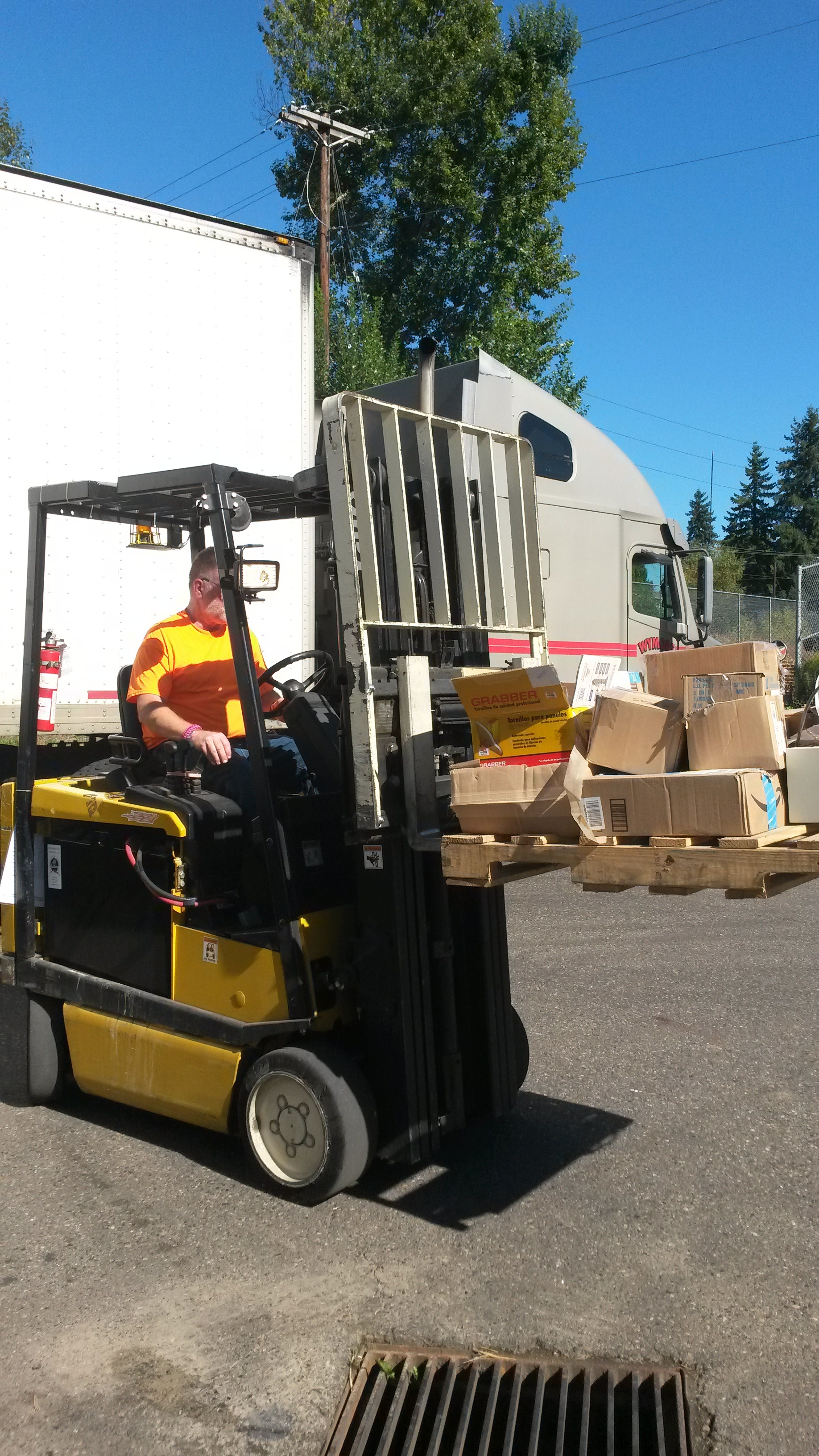A forklift driver at Exceed moving many random items into the warehouse.