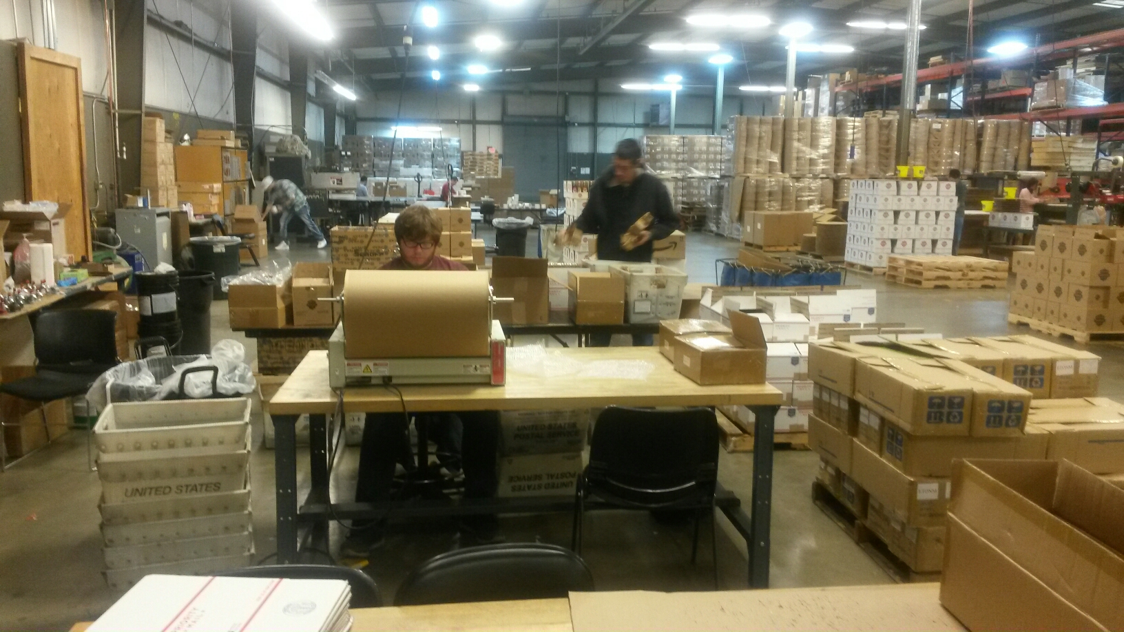 Sean packing boxes and Trevor wrapping the metal brackets