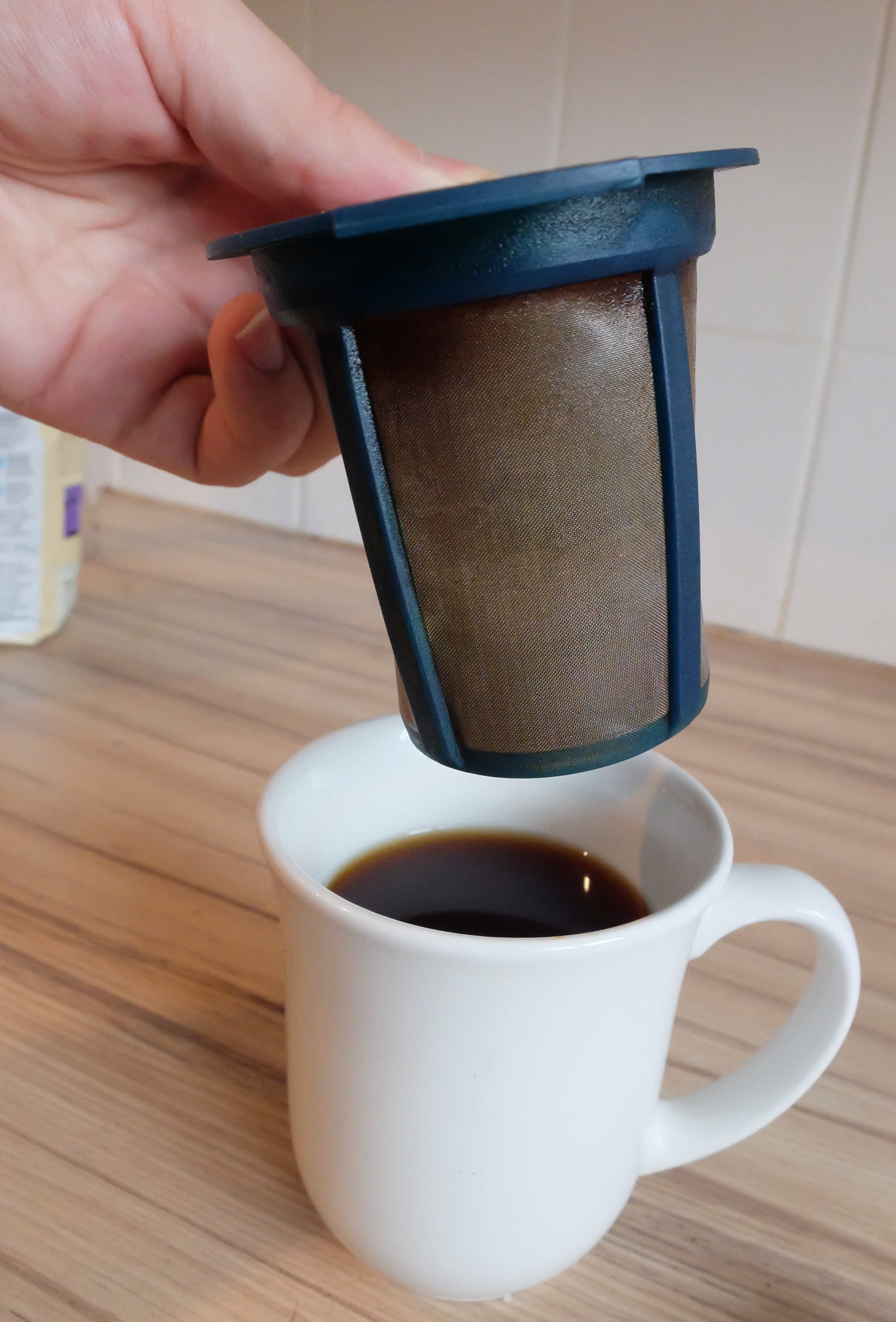 7 - Slowly take the brew basket out of the mug, and let it drip over the mug for a few seconds.
