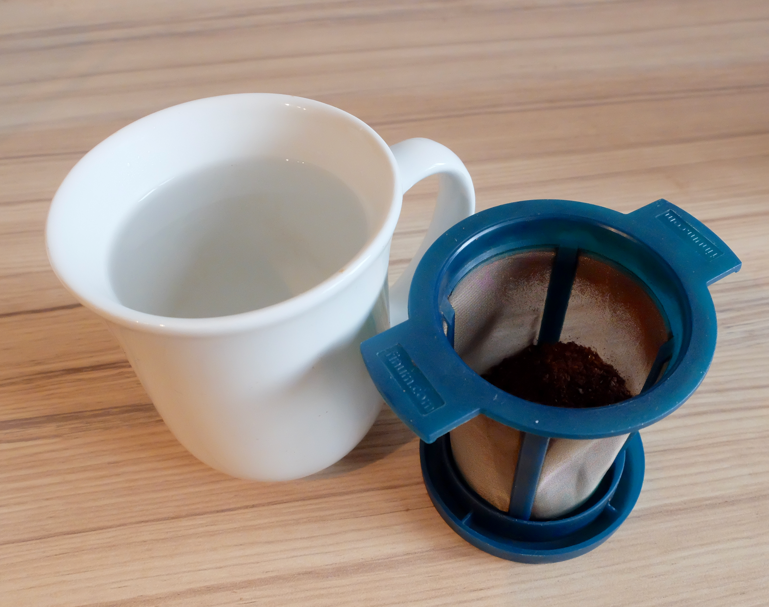 2 - Pour the boiled water into your mug, and allow it to cool to around 95°C (203°F). While the water cools, put the ground coffee into the brew basket.