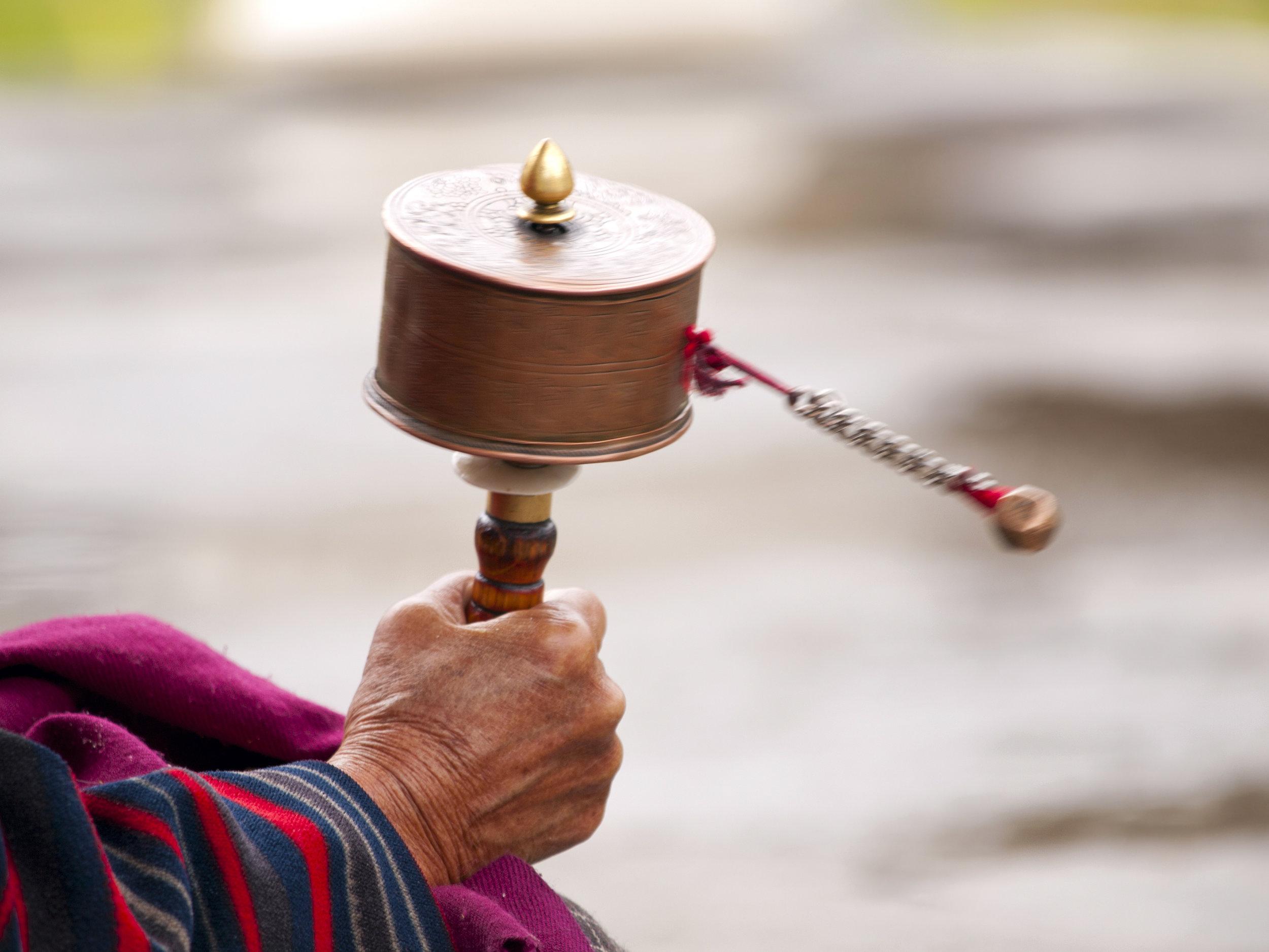 bhutan_bigstock-An-Older-Women-Spinning-Her-Pr-48537116.jpg