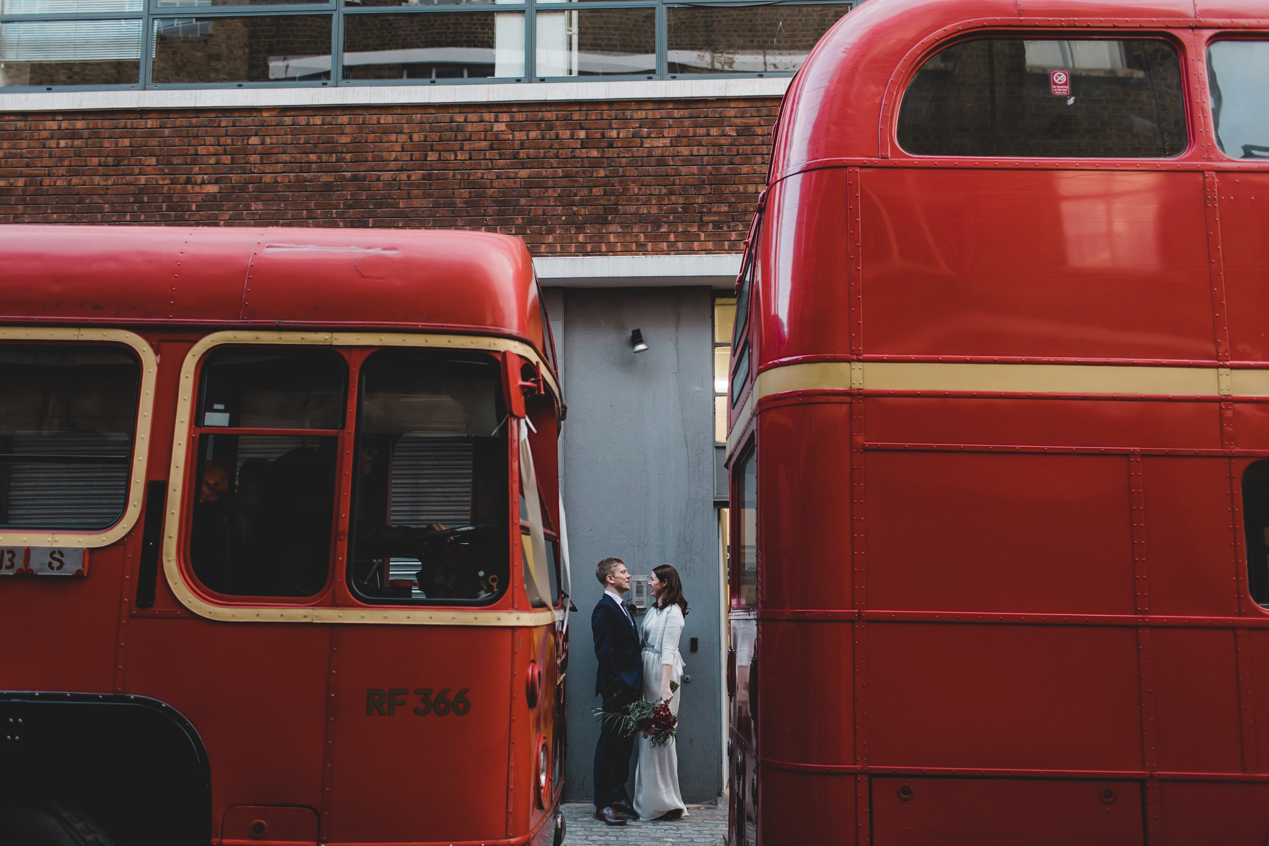 just married couple between two london buses