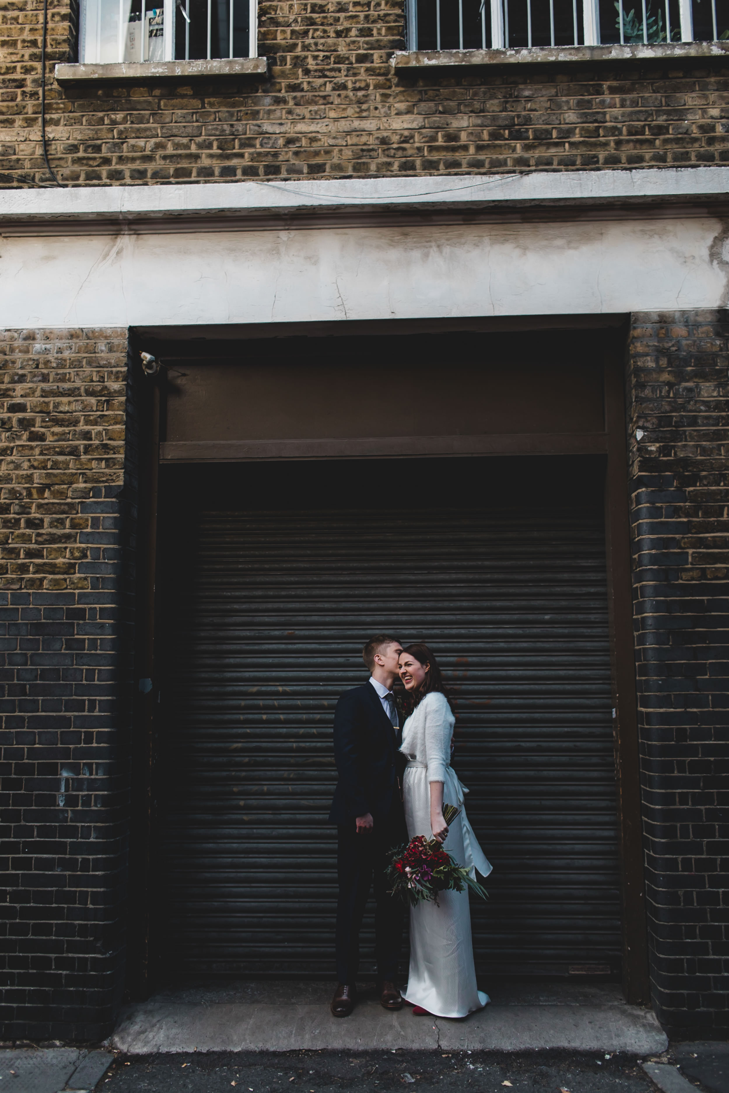 bride and groom pose in front of shutters