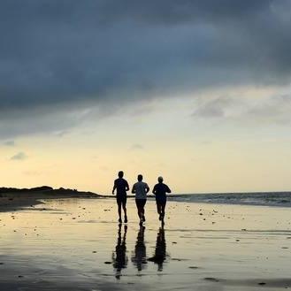25821448-three-men-running-on-the-beach-at-sunrise-bay-of-bolonia-cadiz-province-andalusia-spain.jpg