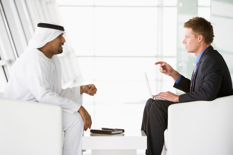 A Middle Eastern man and a caucasian man talking at a business m