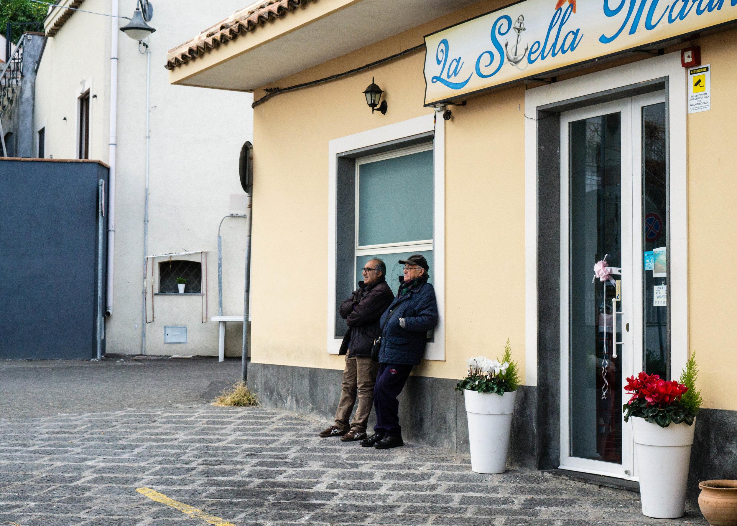 Men in a fishing village talk, Sicily