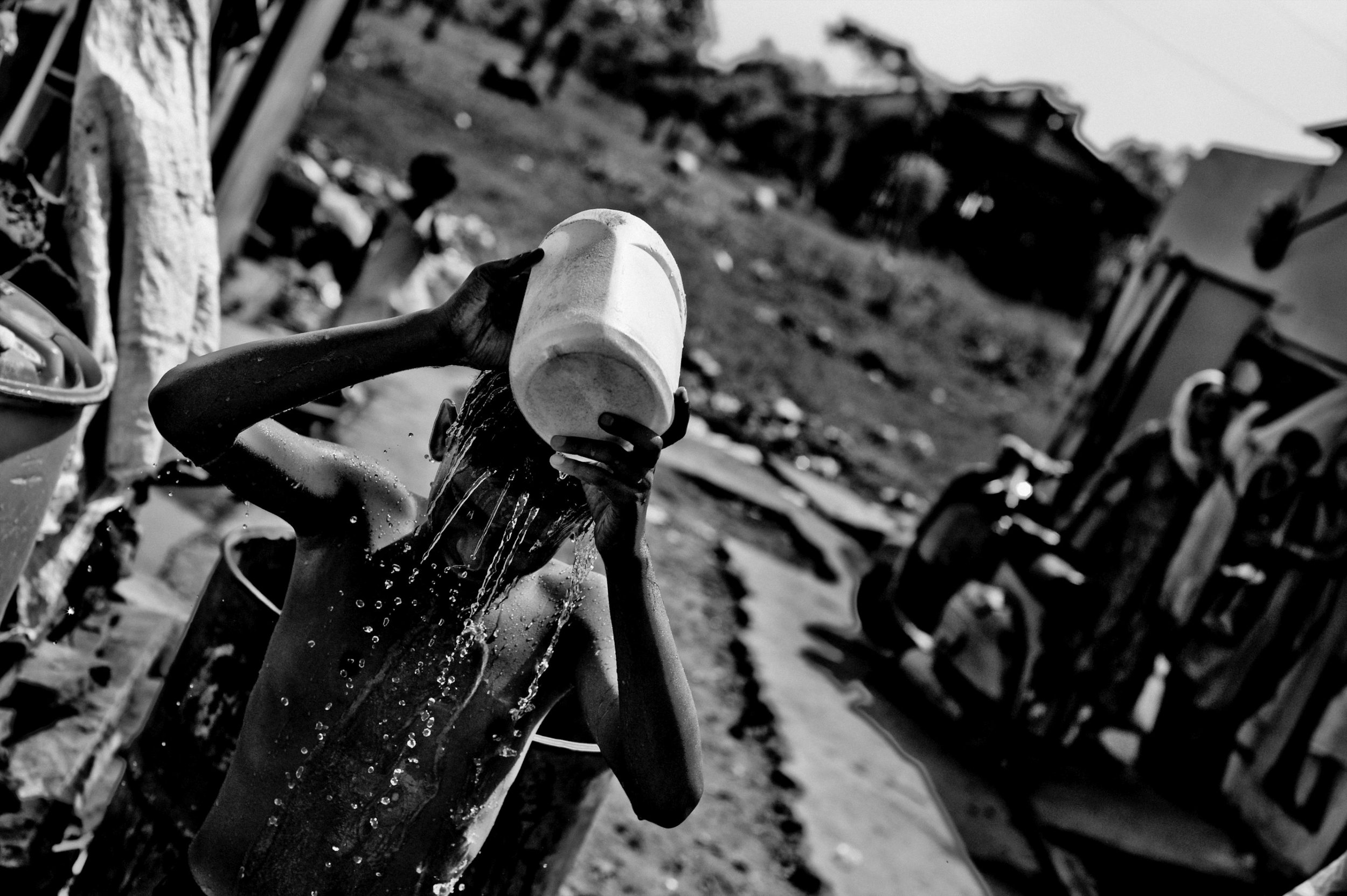 A boy bathes in front of the shack he lives on the site of the Union Carbide plant behind him in the city of Bhopal in the state Madhya Pradesh, India.