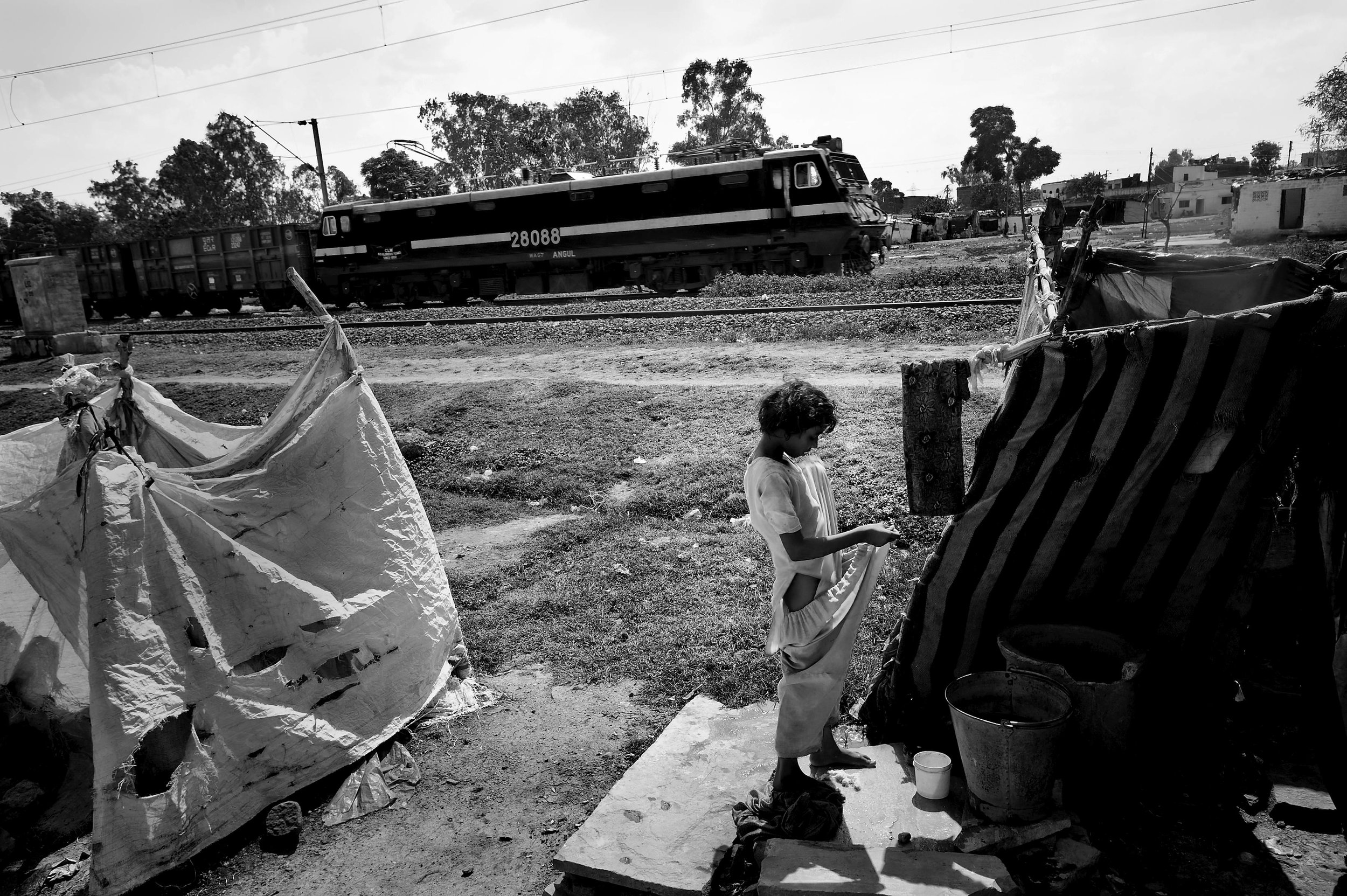 A girl dresses as a train makes its way in front of the shack she lives on the site of the Union Carbide plant behind him in the city of Bhopal in the state Madhya Pradesh, India.