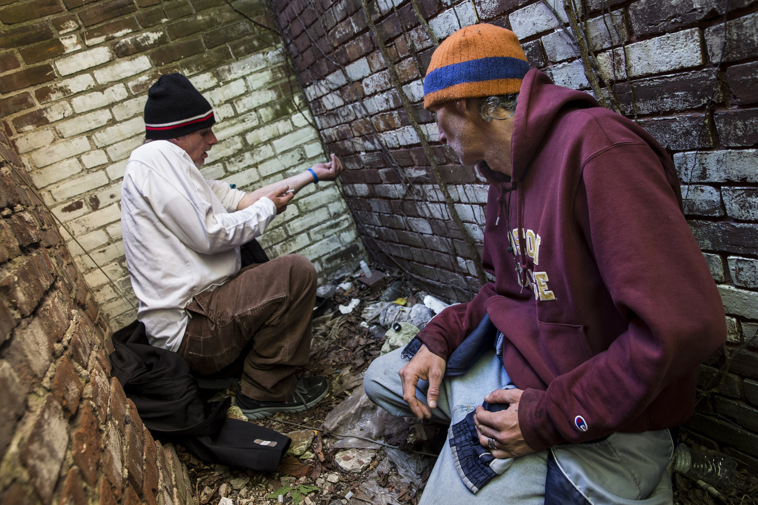 "Shaun ""BoneZ"" LeBlanc(R) watches as his friend Chris shoots heroin behind a house. After a night in the shelter both were feeling the symptoms of withdrawal from heroin usage. Before entering the shelter  users have to discard or hide their drugs or risk being barred if they are caught with them. After spending the night with out a fix Shawn and Chris were desperate to get high. LeBlanc and his wife Donna Perry have been homeless heroin users for the last several years and are working to find housing and kick their habits."