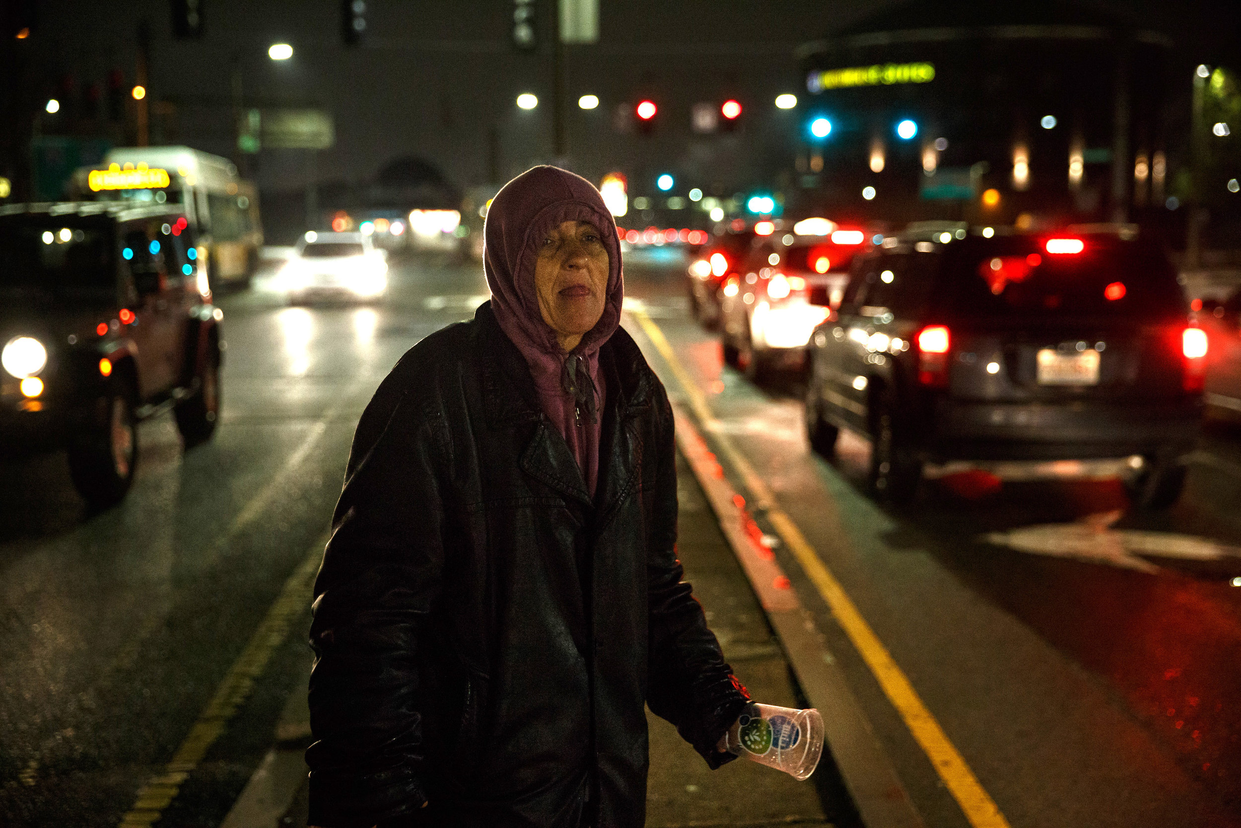 "Heroin addict Shirley Coffey panhandles along a stretch of Massachusetts Avenue known as ""Methadone Mile."" Members of the community take turns walking along the row of cars to ask for money, usually only for as long as it takes to raise enough funds to buy a bag, only to return a few hours later to start the process all over again."