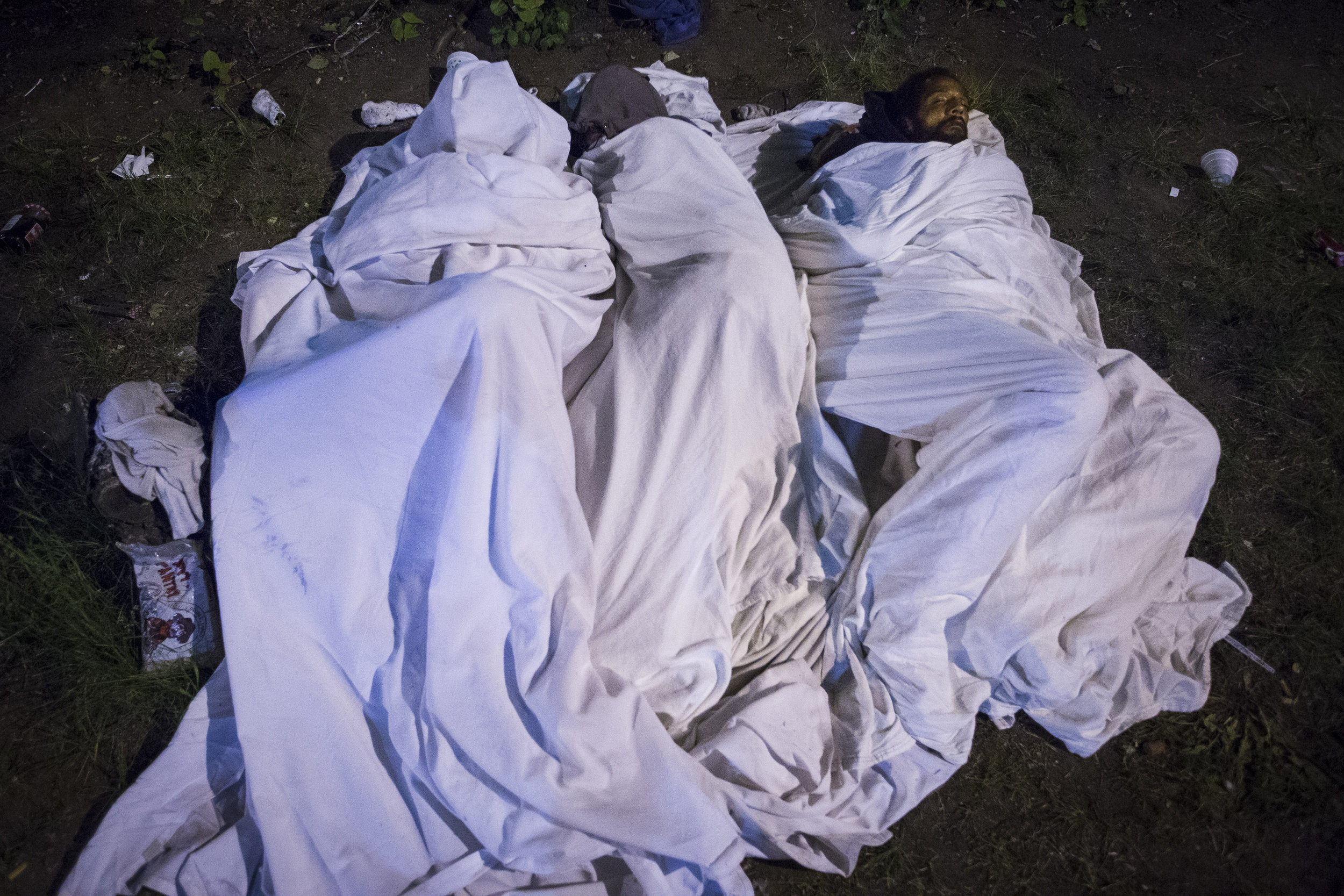 "People wrapped in blankets  sleep along Melnea Cass Boulevard, on ""Methadone Mile."" Sleeping here is dangerous: Thieves snatch bags and rifle through pockets. Some people bed down together on patches of grass, sharing the space for warmth and knowing there is safety in numbers."