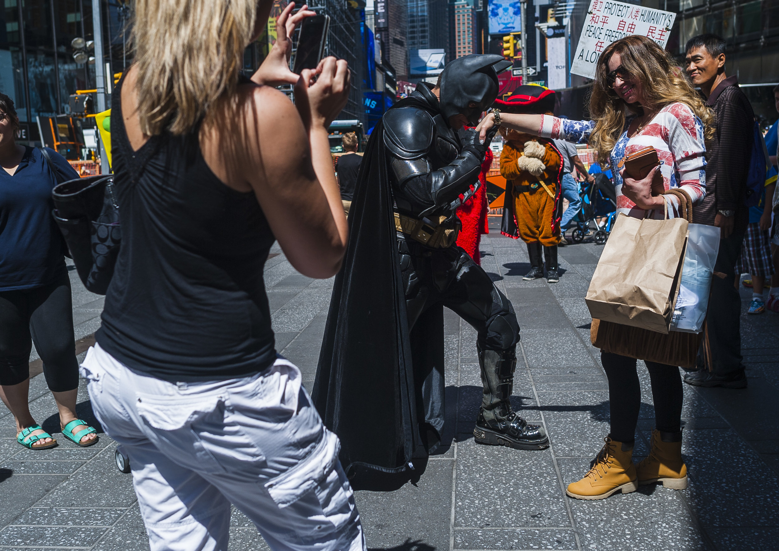 Costumed performer Jose Escalona Martinez kisses a women's hand for a photograph as he works as Batman in Times Square.  Depending on the day, Martinez earns anywhere from $50-$200 per day.