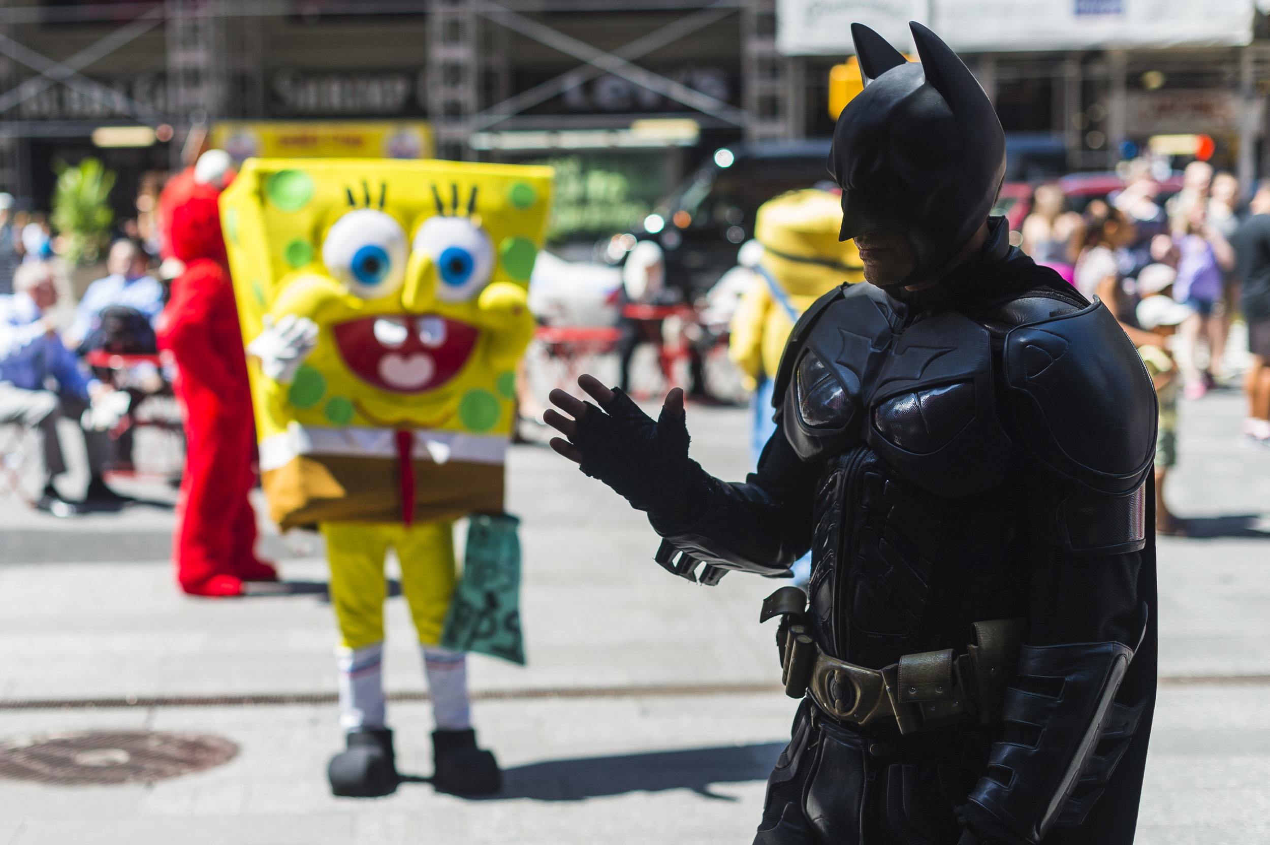 A costumed Sponge Bob watches as Jose waves to passersby.