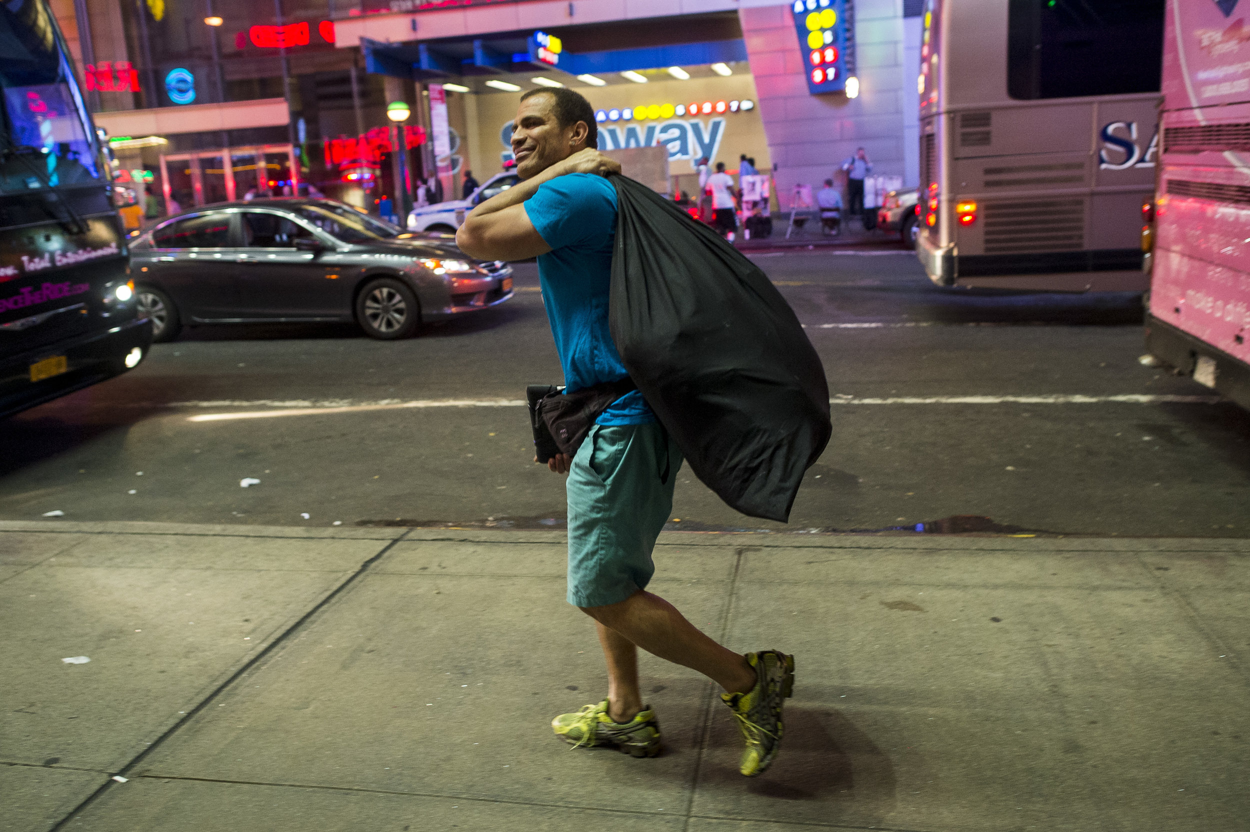 Jose carries his Batman costume as he makes his way towards home at the end of his shift in Times Square.