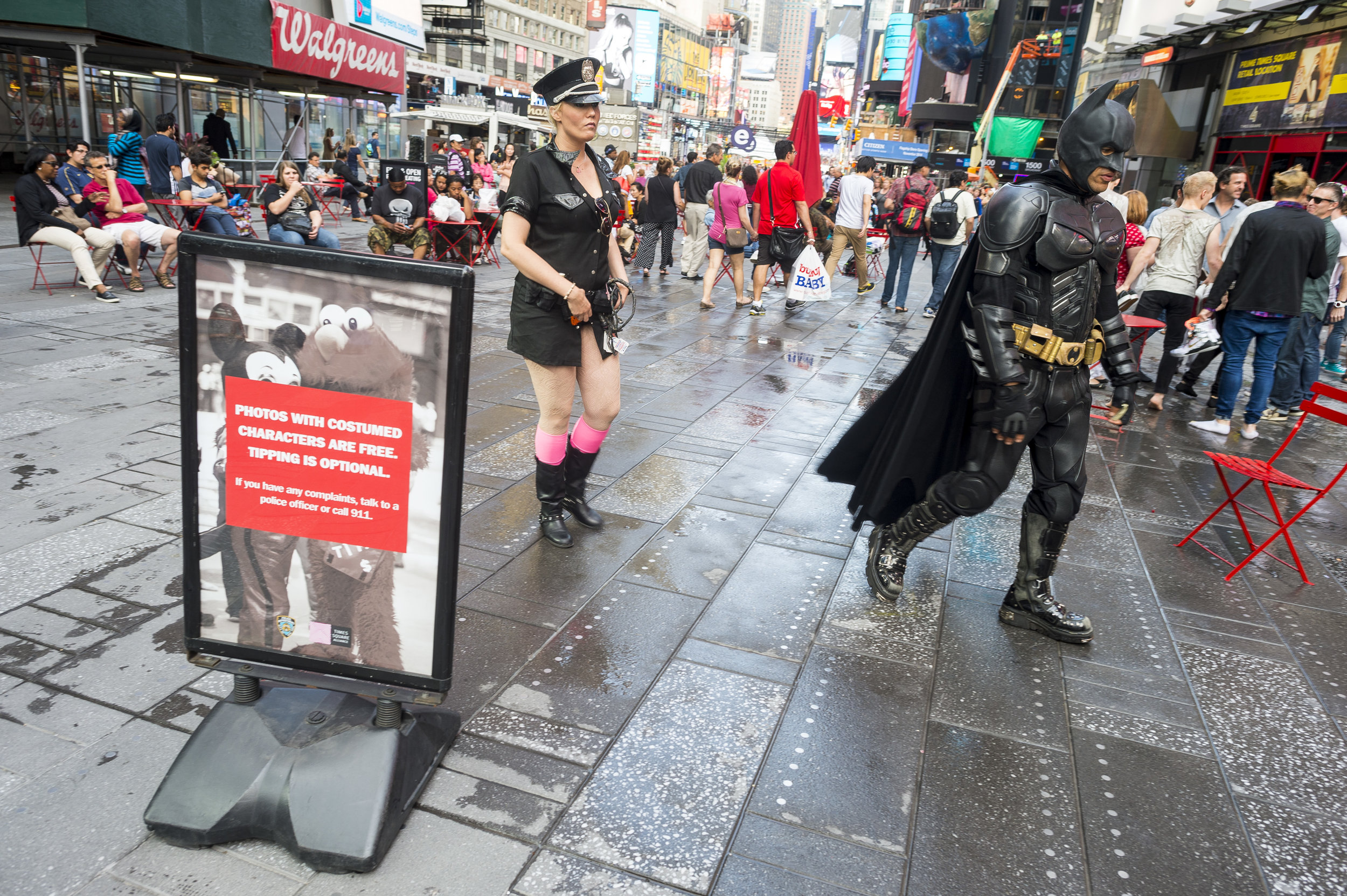 Jose and his girlfriend and fellow performer Elizabeth walk past a sign displaying rules for tipping costumed characters during his shift as Batman in Times Square.
