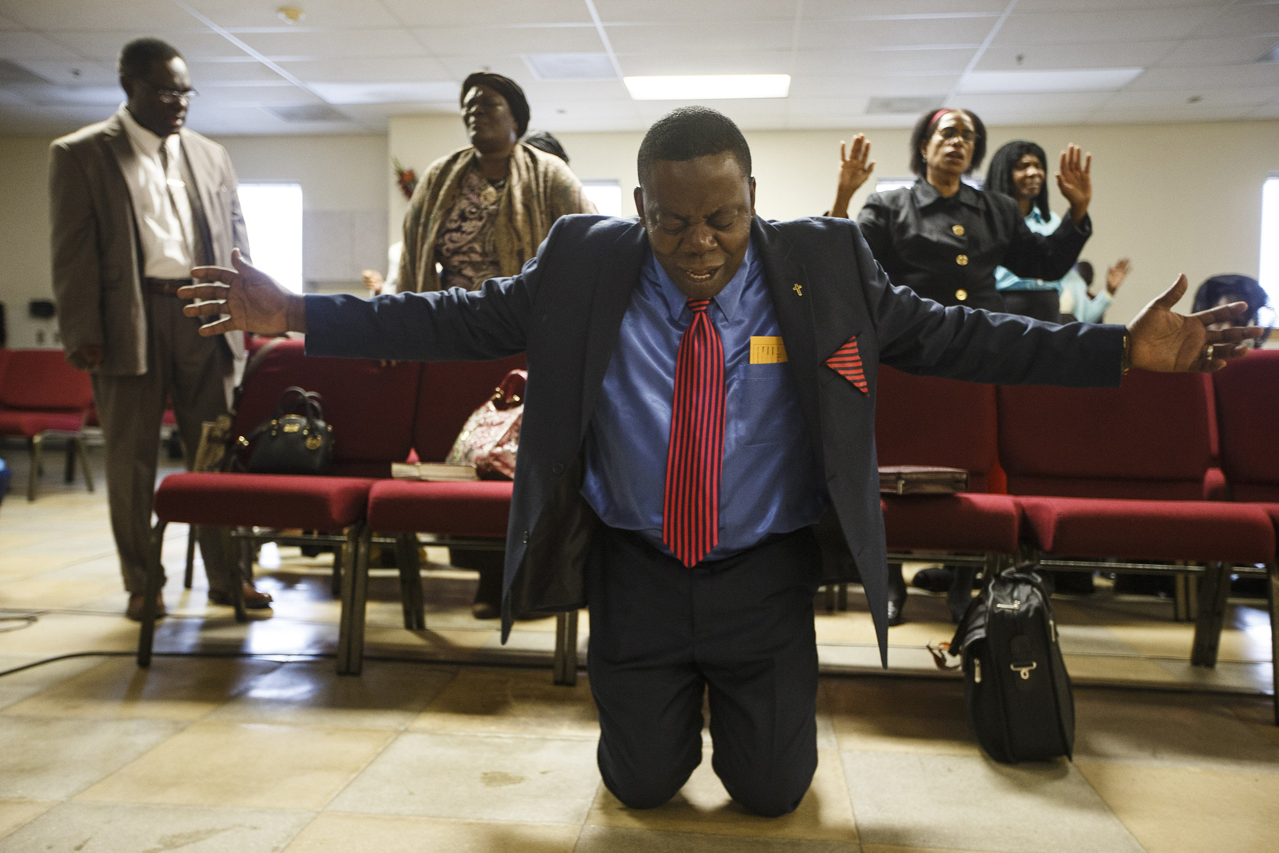 Pastor Jean Jeune leads congregants prays for hurricane victims during service at the First Christian Church Source of Grace, a church frequented by the Haitian community, in Boston, MA, October 9, 2016.    Several members of the church have family and friends affected by the destruction Hurricane Matthew left in Haiti.