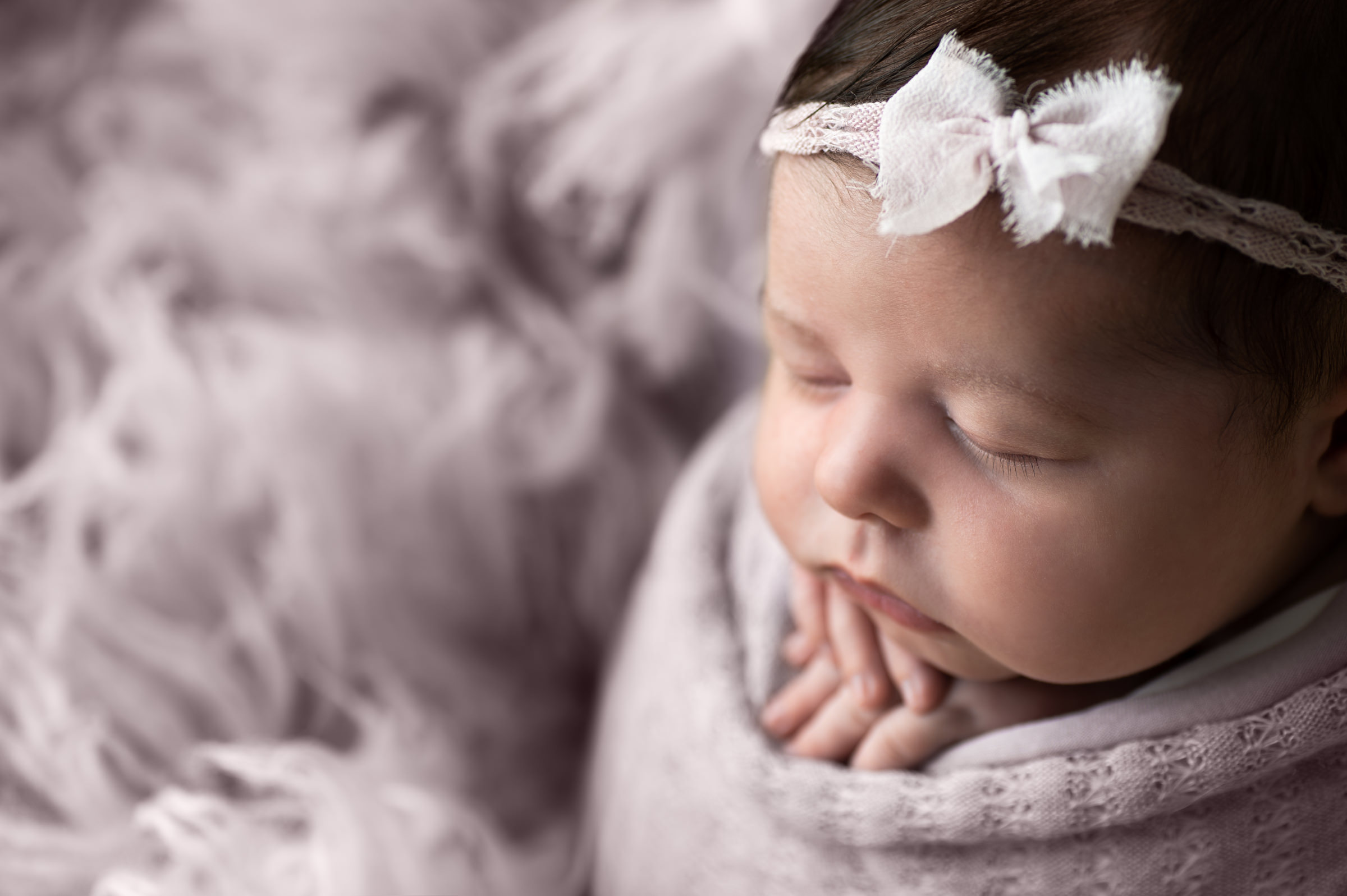 close up of newborn girl in lavender in potato sack pose wearing a bow