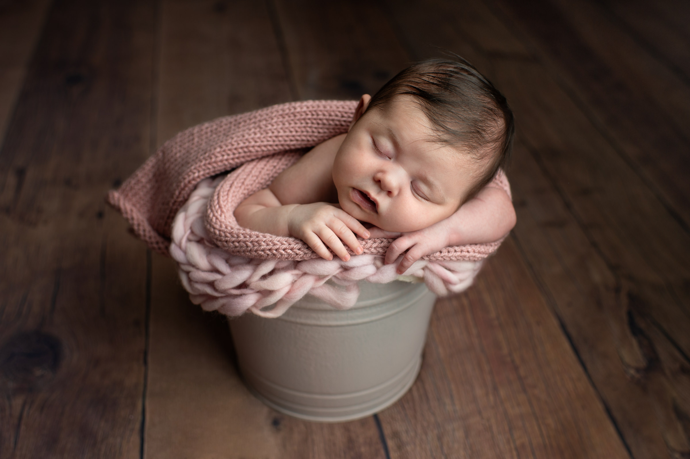 Newborn girl in a bucket at an in-home studio session in Danbury, CT