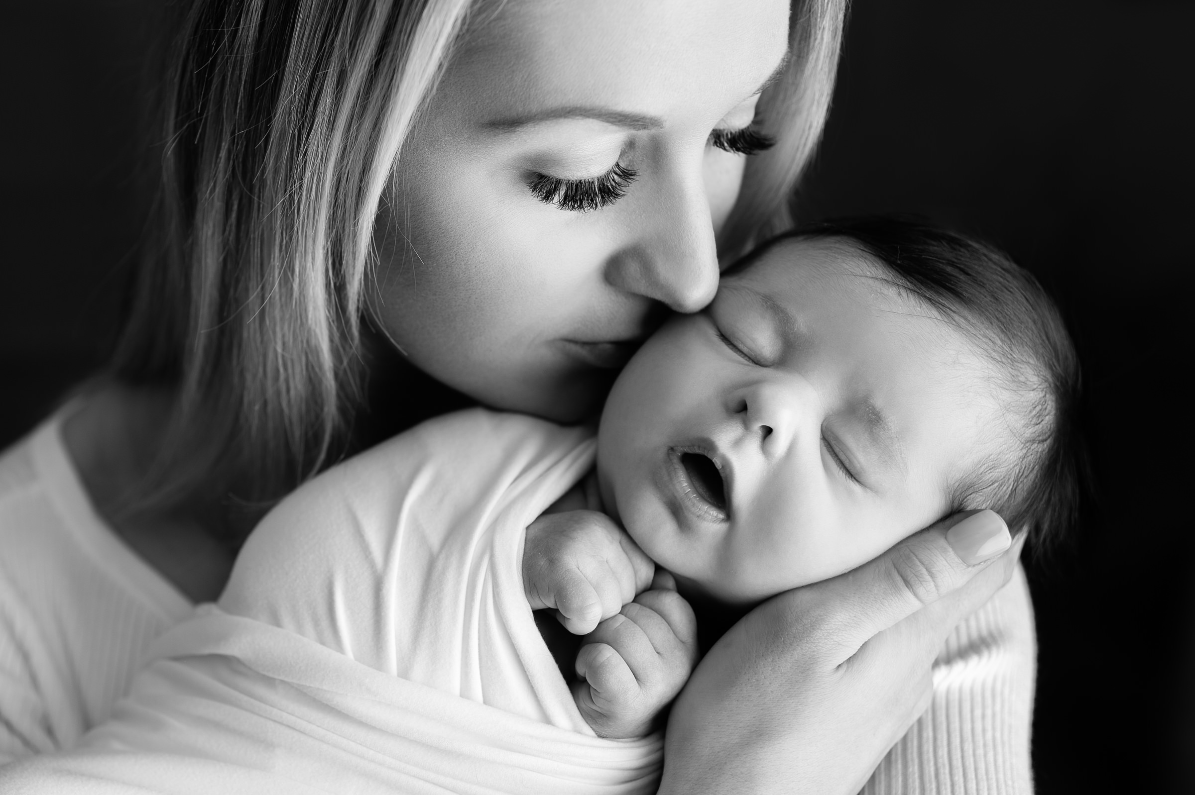 Newborn girl wrapped in white being kissed by mom looking down in black and white