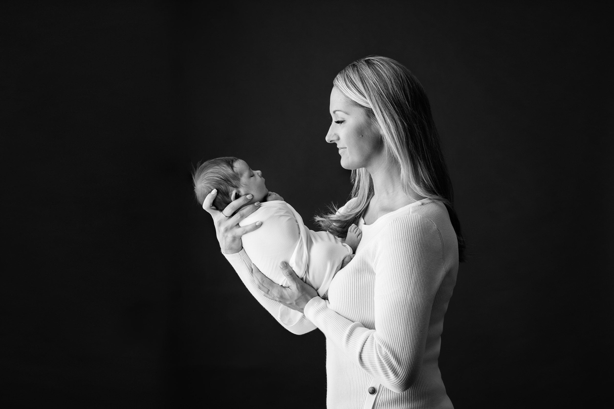 Newborn girl being held by mom wearing white in black and white