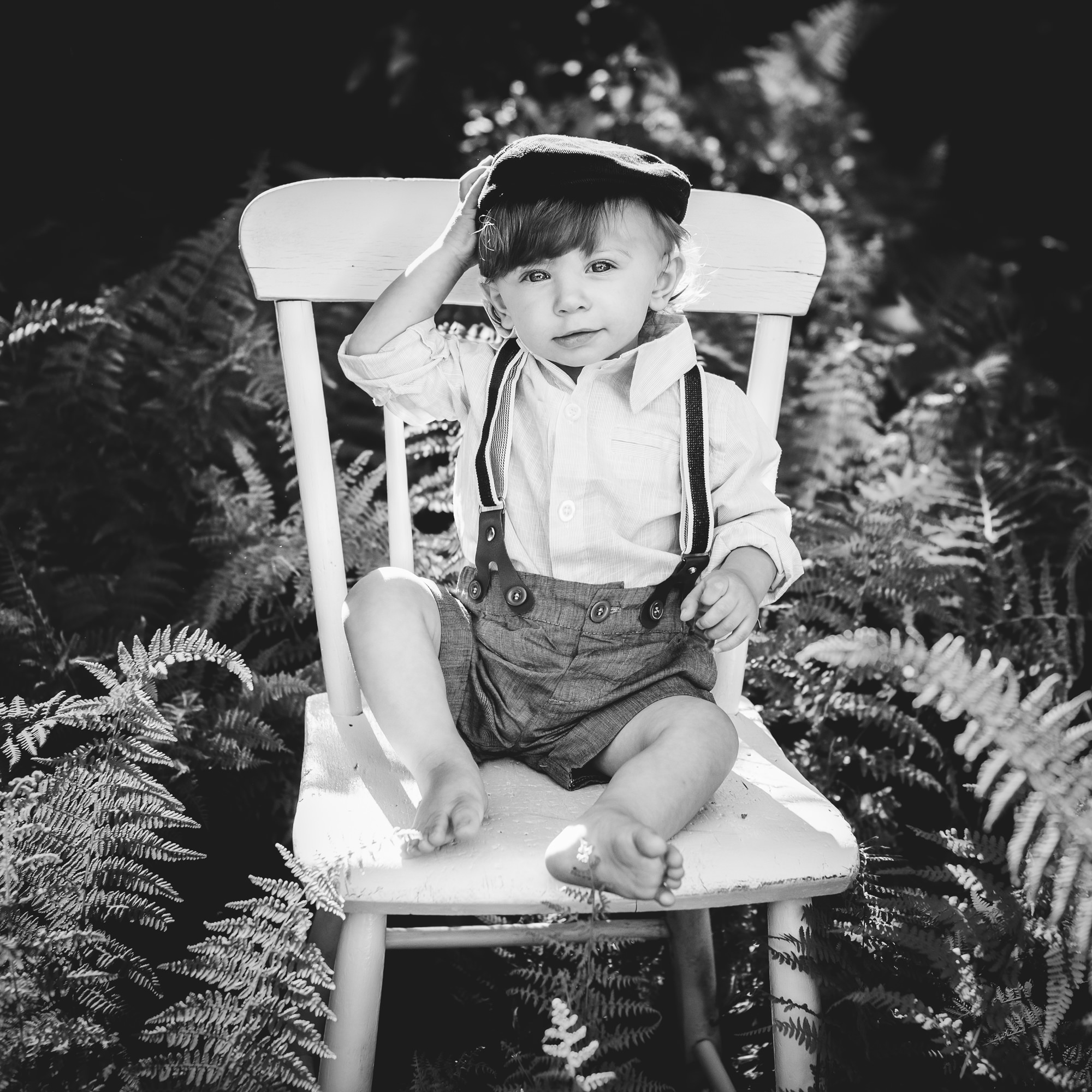 one year old boy sitting on a chair in the ferns outside in connecticut