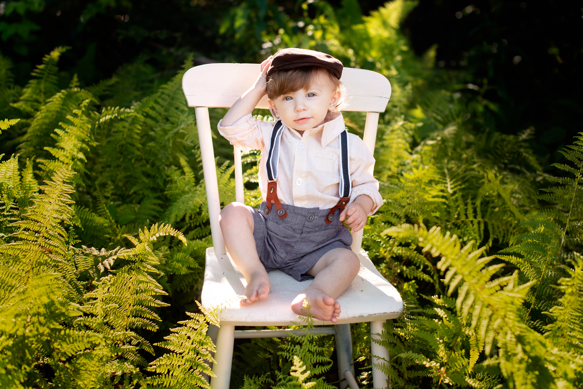 one year old boy sitting on an antique chair in a field of ferns in killingworth, ct