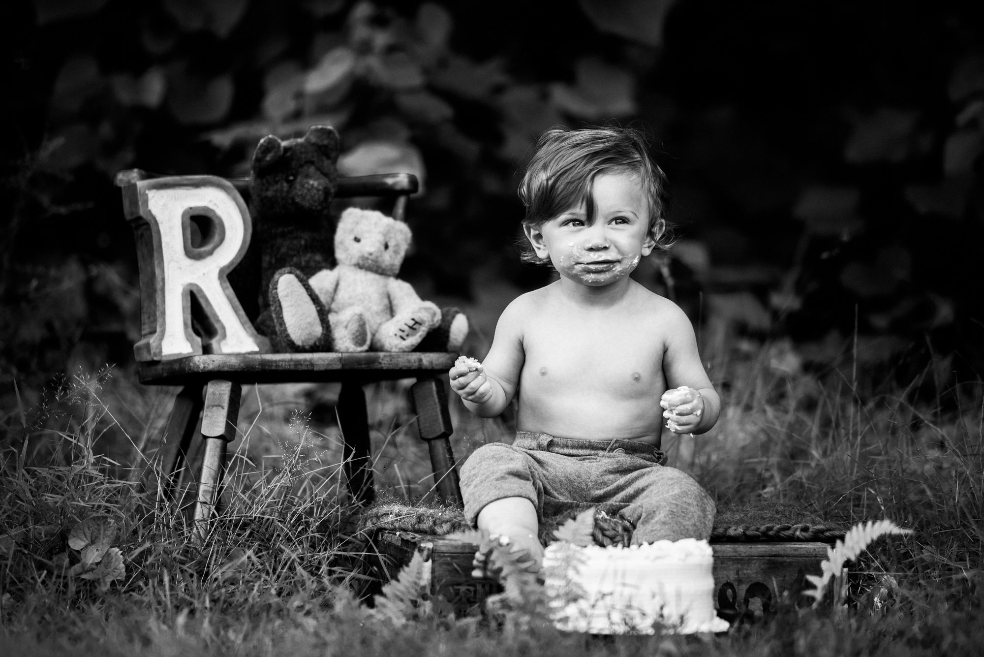 black and white image of a one year old boy eating his cake during his outdoor cake smash