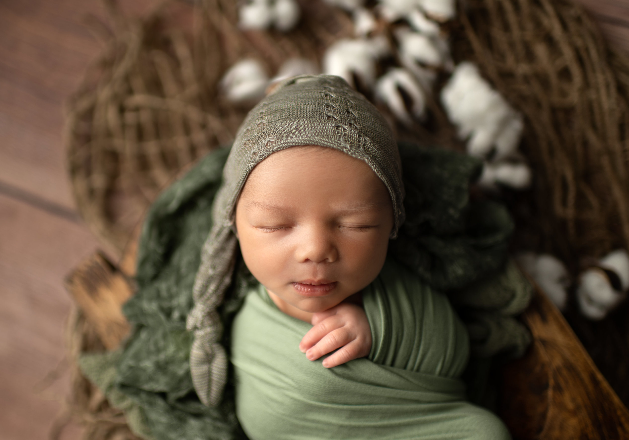 rustic newborn boy wrapped in green with cotton and a sleepy cap