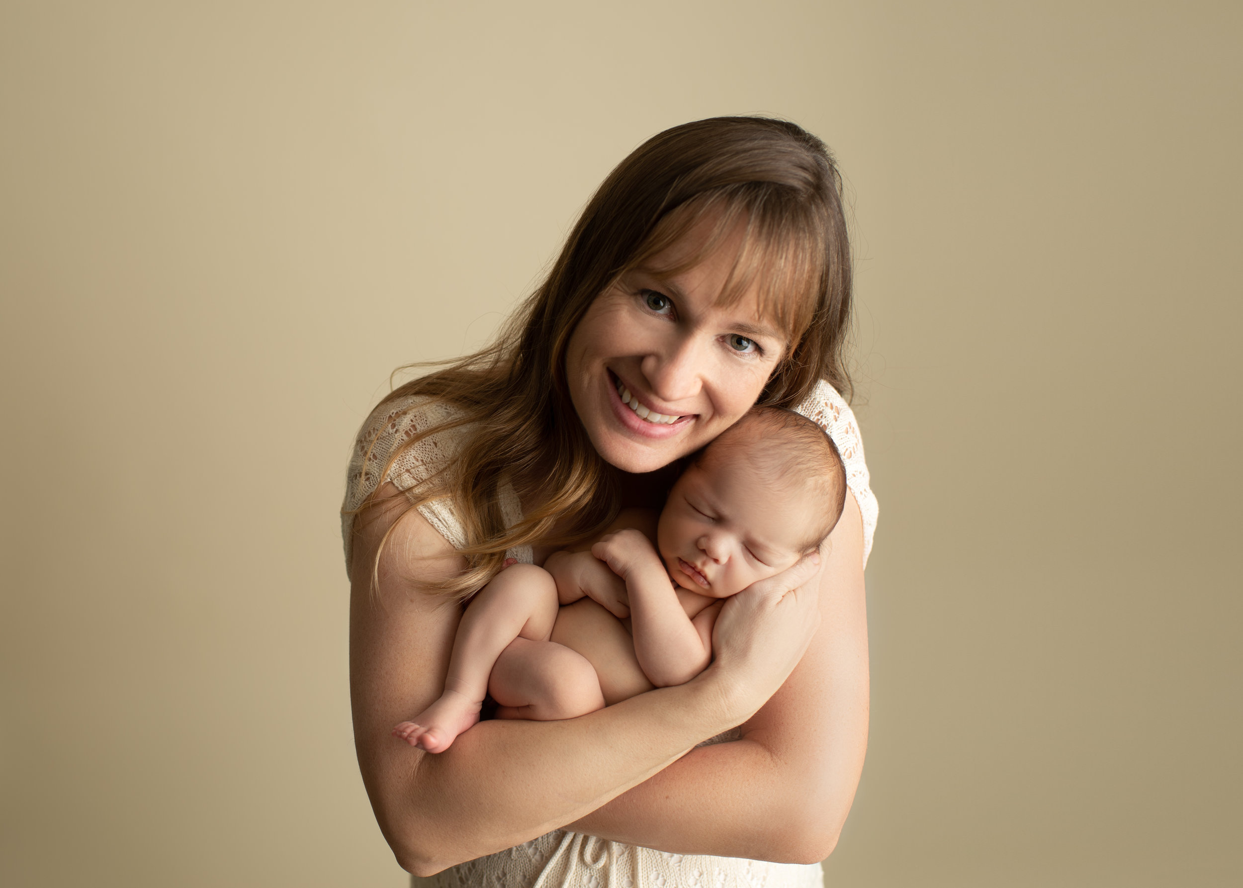 proud mom smiling at camera with newborn boy
