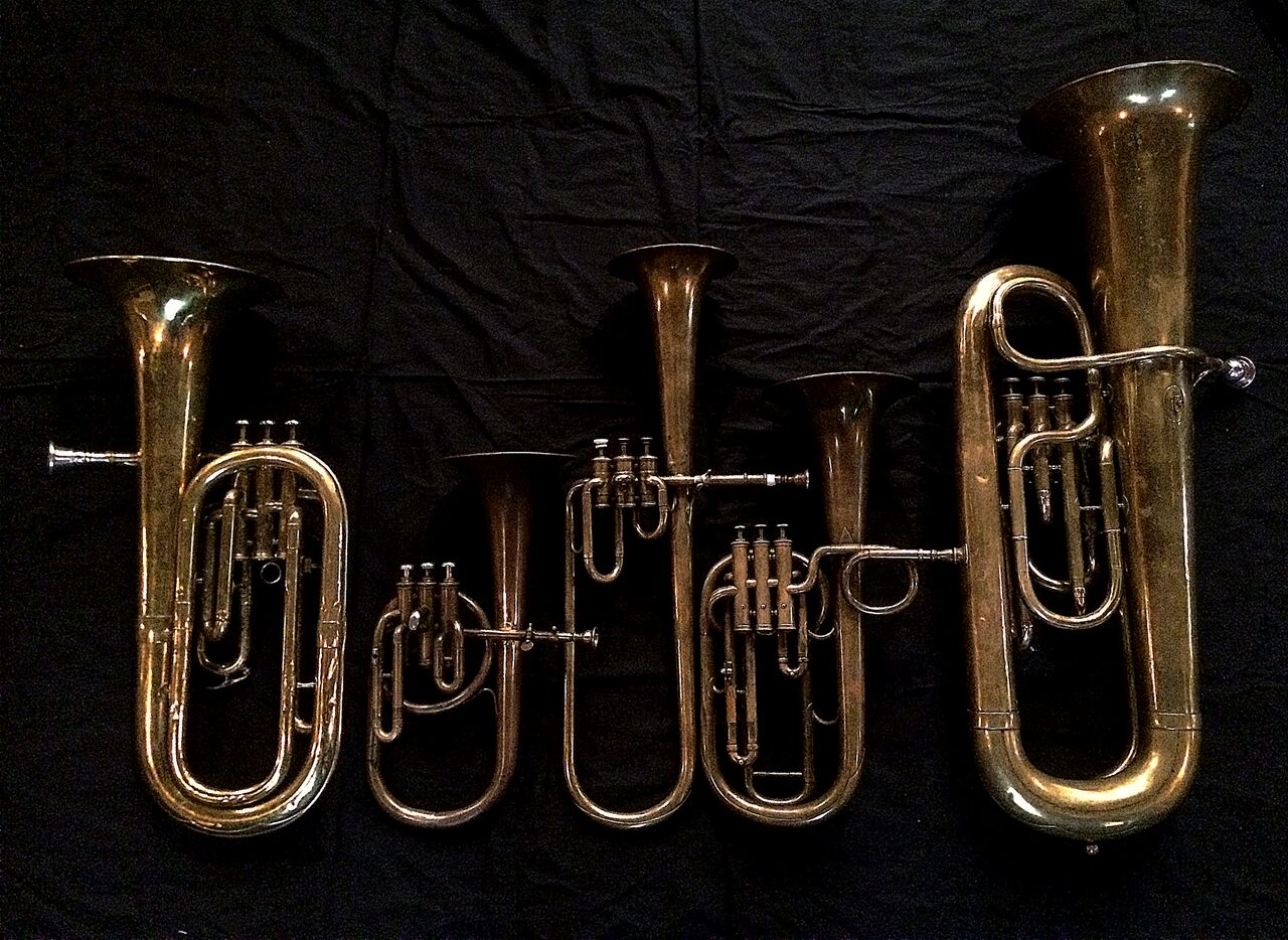 Left to Right:  Baritone saxhorn in B-flat   by Couesnon (44139, 94 Rue D'angouleme Exposition Universelle De Paris, 1900) ,  Contralto saxhorn in B-flat   by J. Grass (32 Rue des Ponts de Comines, Lille, est. 1868,   Contralto saxhorn in B-flat   by Adolphe Sax (Paris, c. 1849-1850), sold by Distin & Sons, Cranbourne St. Leicester Square, London,   Tenor saxhorn in F/E flat/D     by Antoine Courtois (Paris, c. 1855), sold by Arthur Chappell (London),   Contrabass saxhorn in E-flat   by E. Daniel (7167, Marseille, c. 1850).