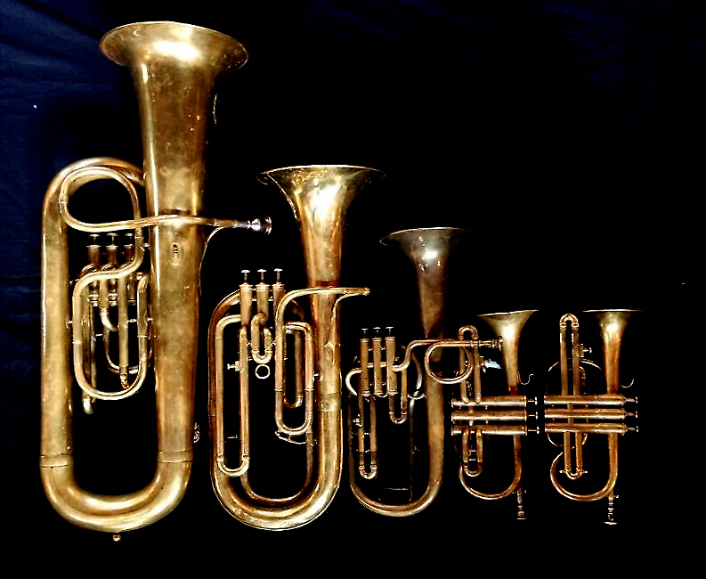 Left to Right:   Contrabass saxhorn in E-flat   by E. Daniel (7167, Marseille, c. 1850).   Baritone saxhorn in B-flat   by Couesnon (44139, 94 Rue D'angouleme Exposition Universelle De Paris, 1900),   Tenor saxhorn in F/E flat/D   by Antoine Courtois (Paris, c. 1855), sold by Arthur Chappell (London),     Cornet in B-flat/A   by Couesnon (no makers address or serial number, Paris),     Cornet in B-flat/A     F. Besson (44292, 96 Rue D'angouleme, Paris c. 1892).